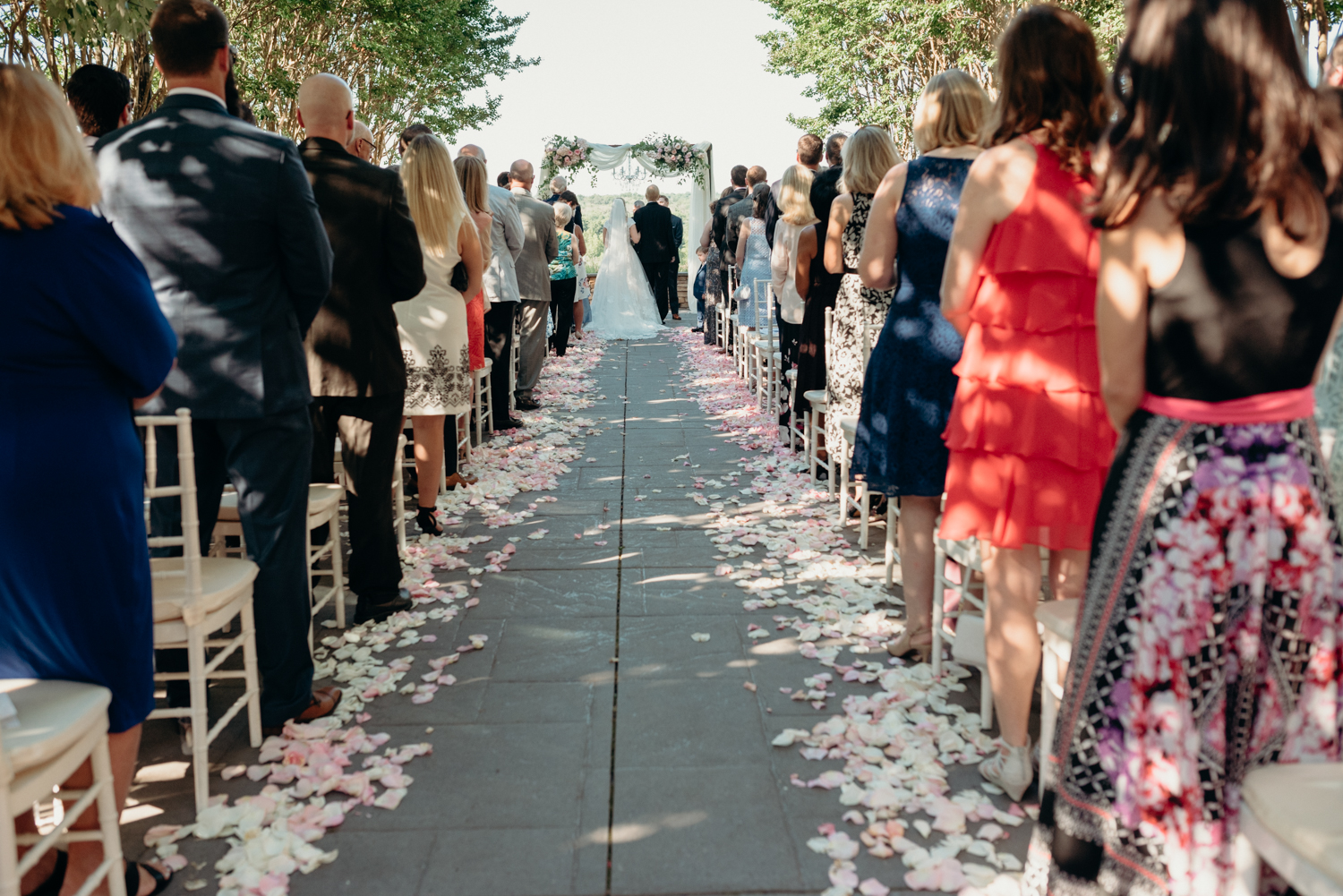 A crowd of guests looks down an aisle lined with rose petals during a wedding ceremony at Lansdowne resort.