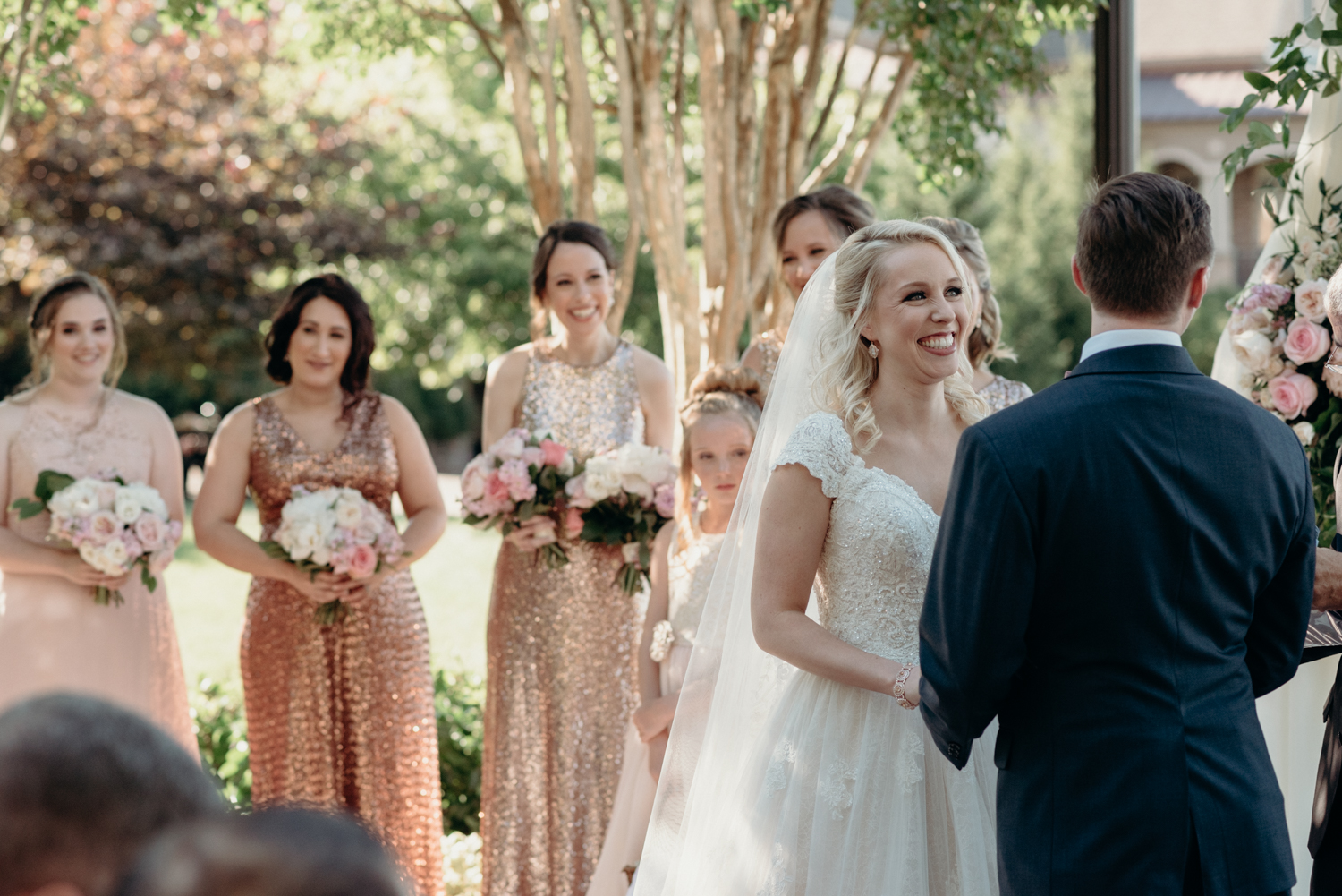 A bride smiles at her groom while her bridesmaids in sparkly dresses look on during a wedding ceremony at Lansdowne Resort.