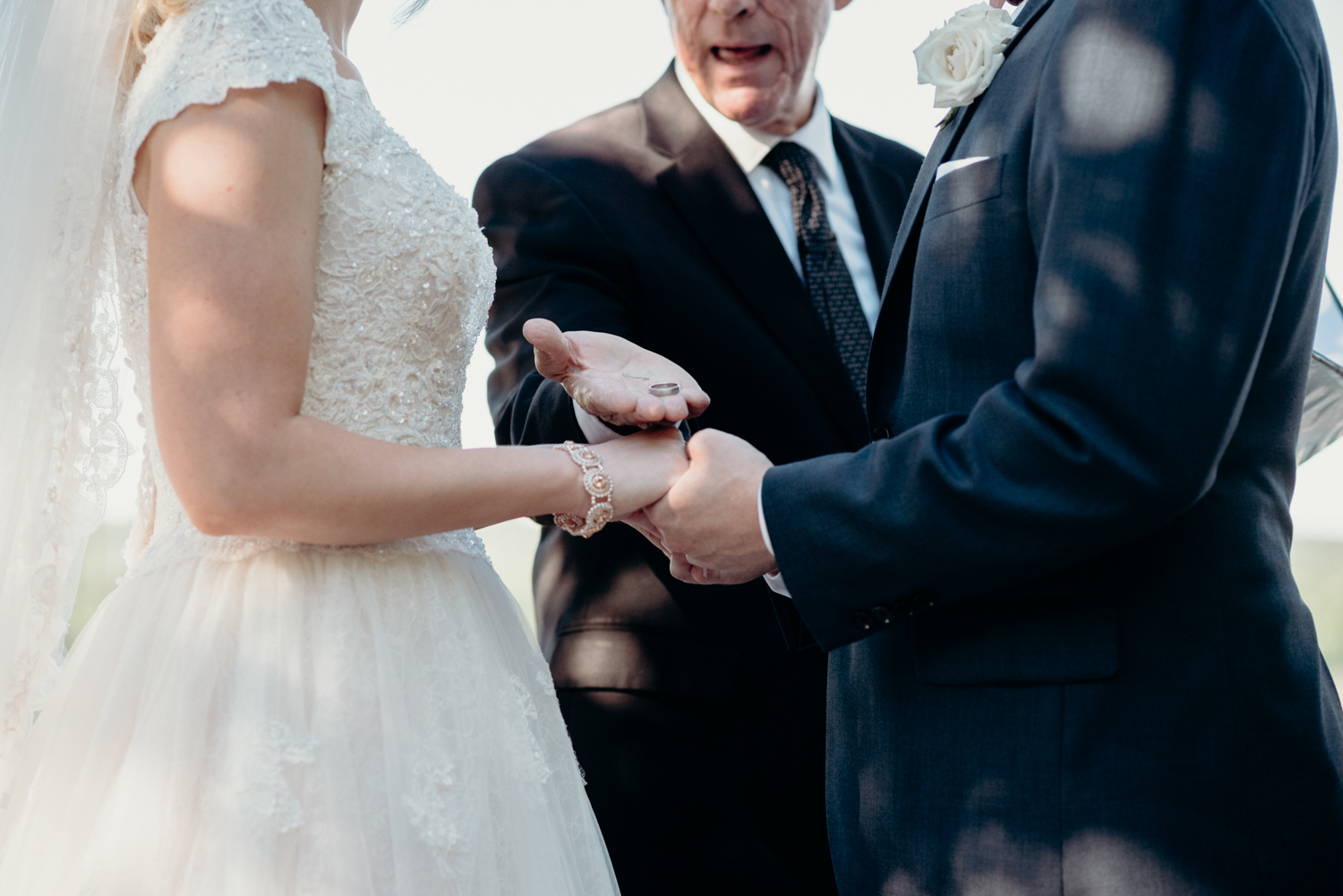 An officiant hands the bride and groom their rings during a ceremony at Lansdowne Resort.
