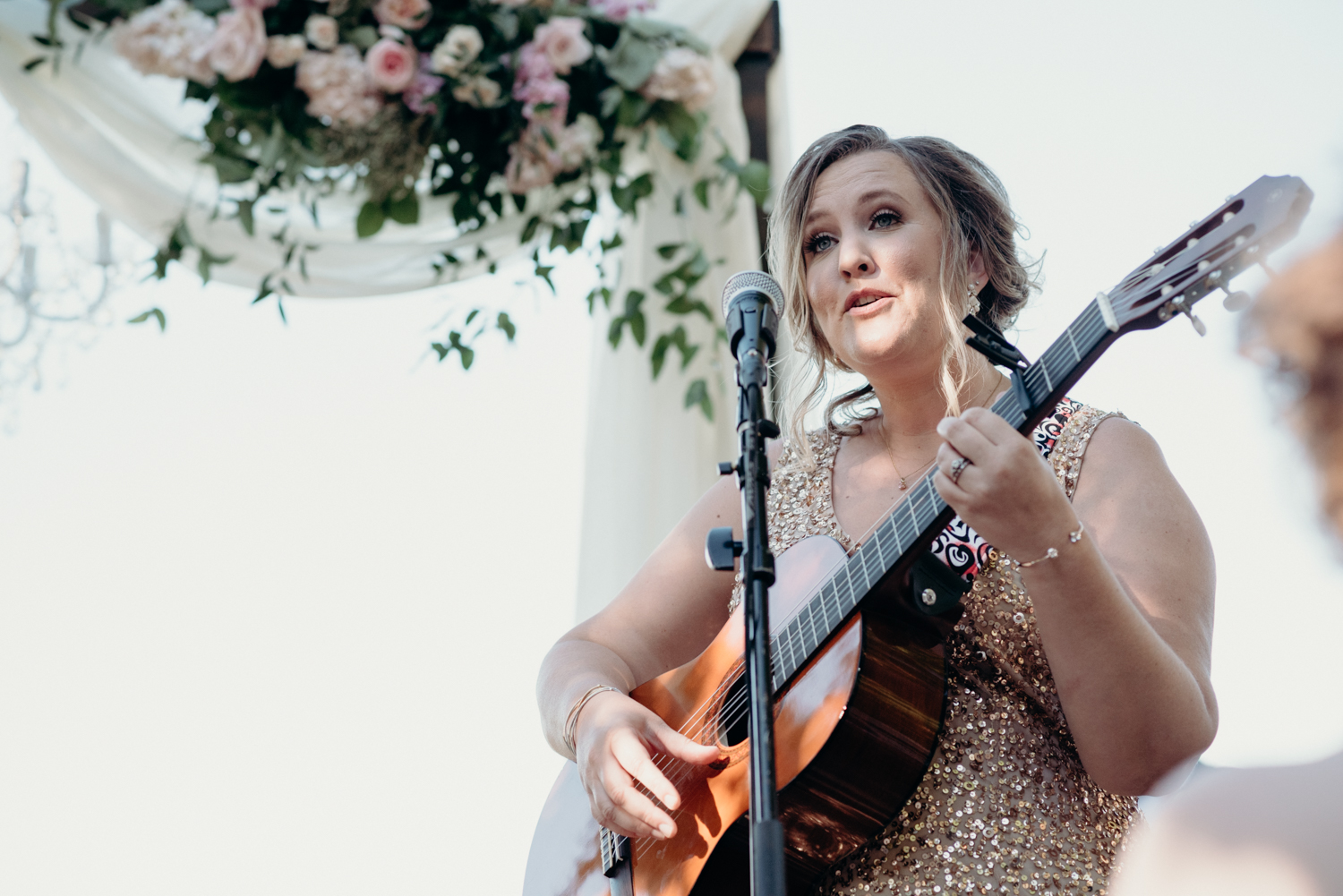 A bridesmaid performs a song during her sisters wedding ceremony at Lansdowne Resort.