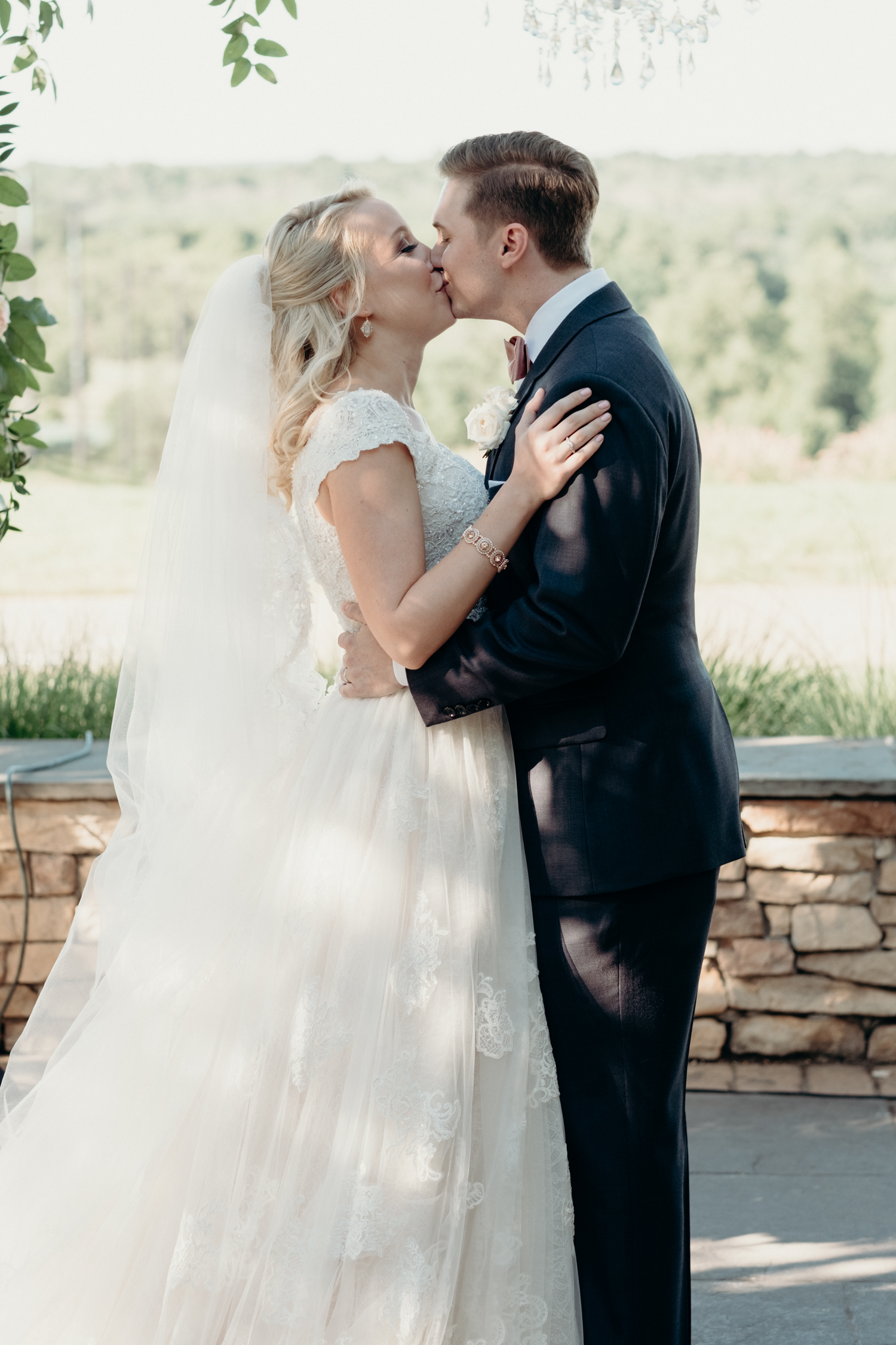 A bride and groom share their first kiss during their outdoor wedding ceremony at Lansdowne Resort.