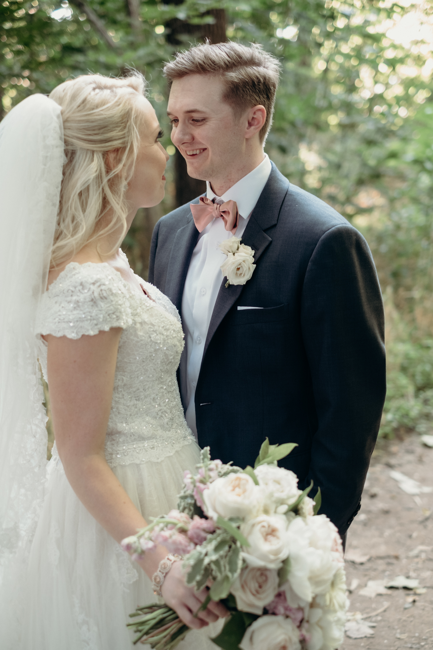 A bride carrying a bouquet of white and pink flowers looks into the eyes of her groom in a peach bowtie in the woods at Lansdowne Resort and Golf Course.