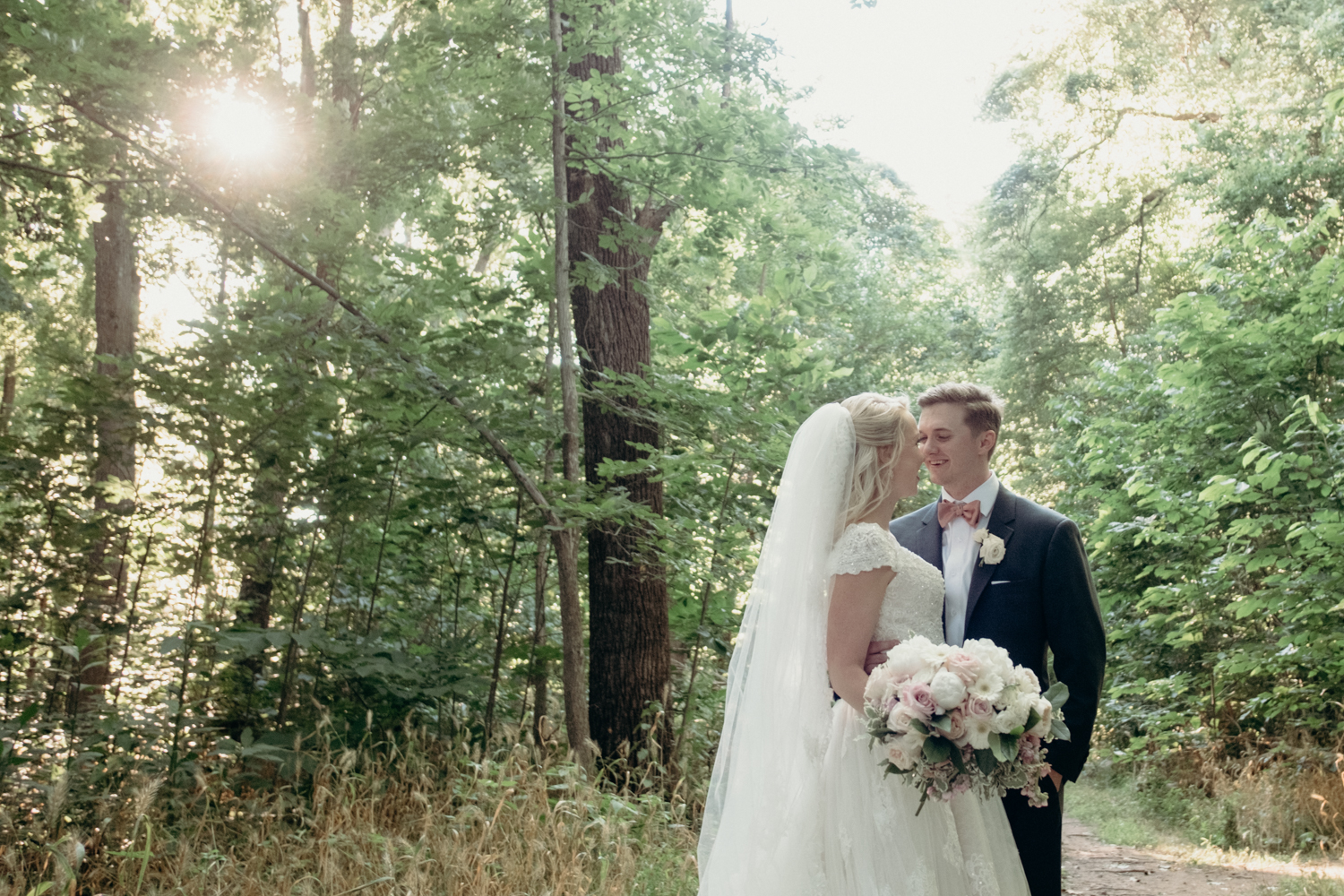 A husband and wife smile at one another in the woods after their outdoor wedding ceremony at Lansdowne Resort.