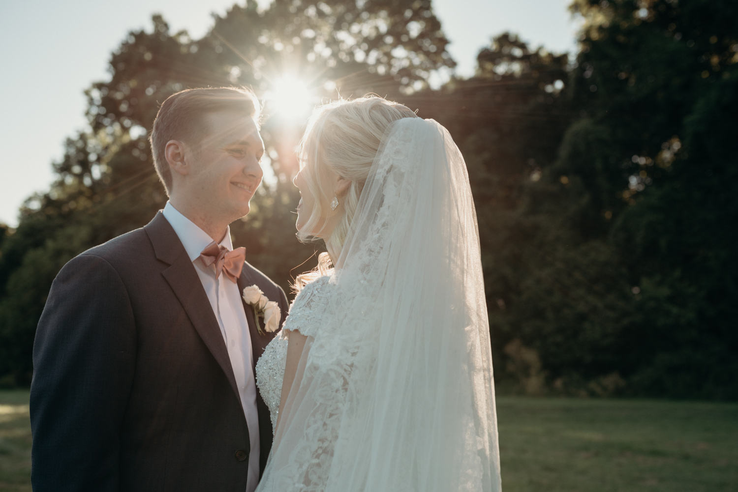 The sun shines through while a husband and wife gaze at each other after their outdoor wedding ceremony at Lansdowne Resort.
