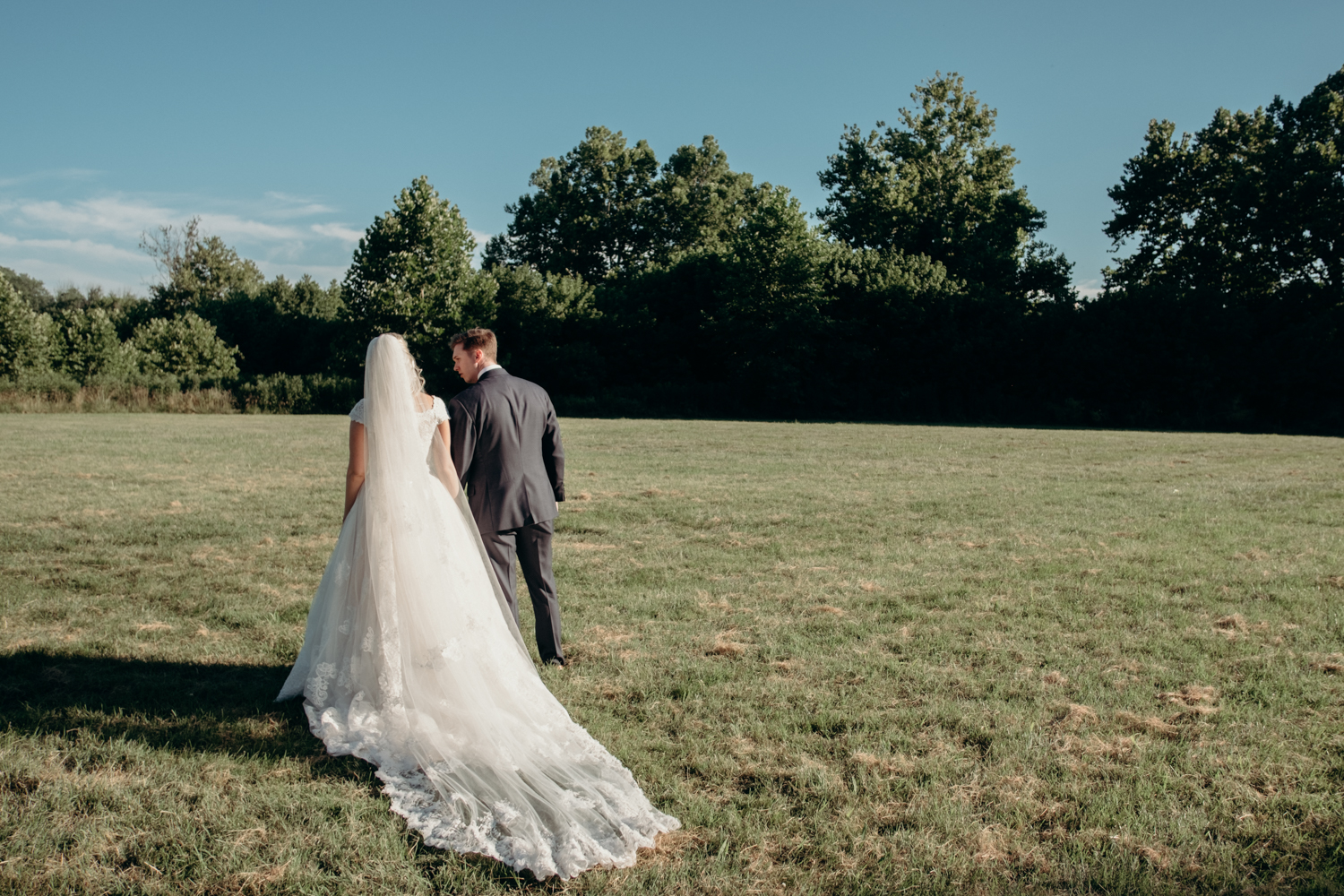 A husband and wife walk through a field in the sunshine after their outdoor wedding ceremony at Lansdowne Resort.