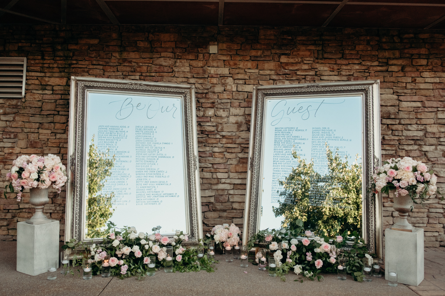 A seating chart for guests at a wedding reception is written on two large mirrors surrounded by lush florals.