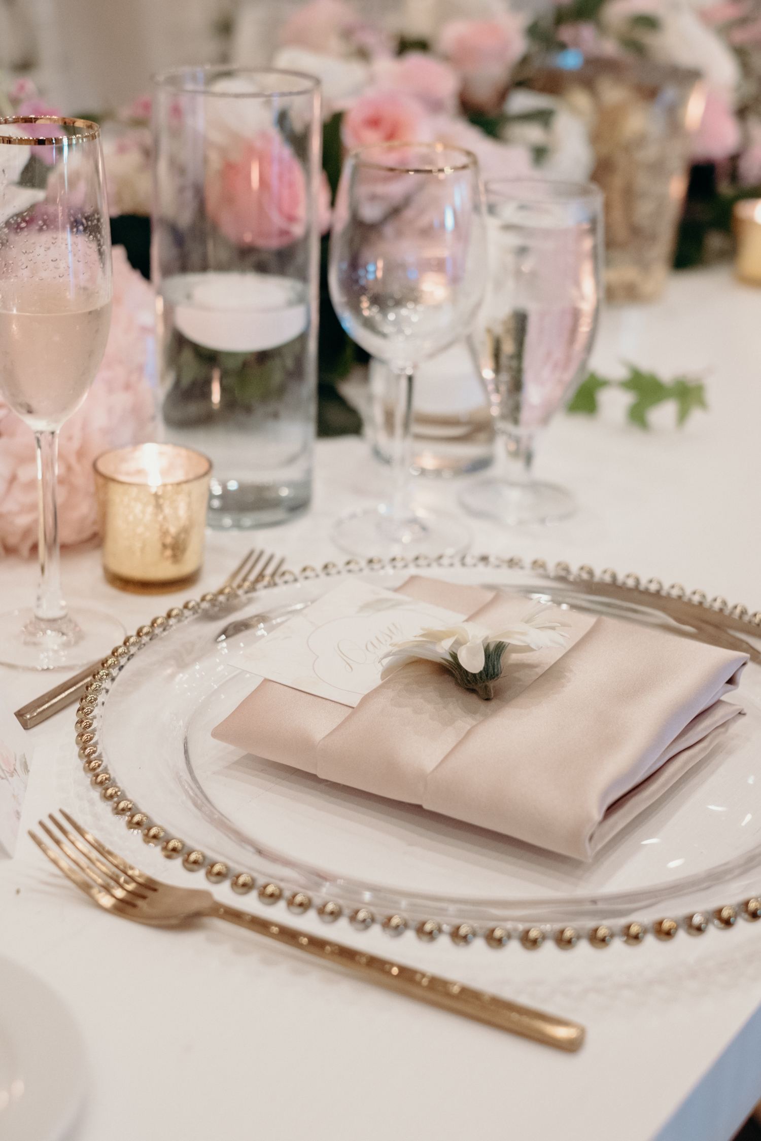 A cream and blush table setting is accented with a white daisy and menu at a wedding reception at Lansdowne Resort.