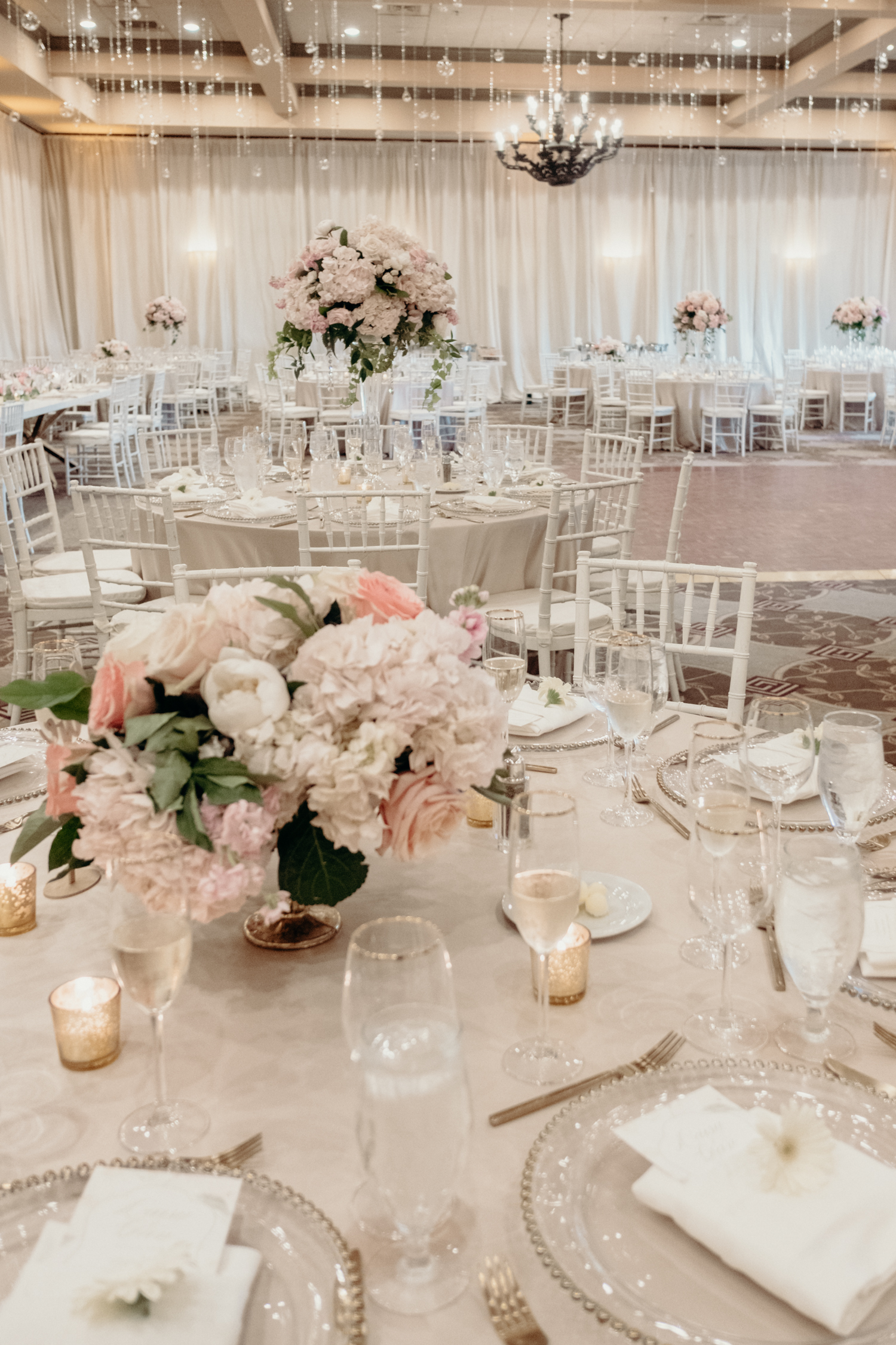 A ballroom at Lansdowne Resort is decorated in whites and creams and pinks with crystals dripping from the ceiling.