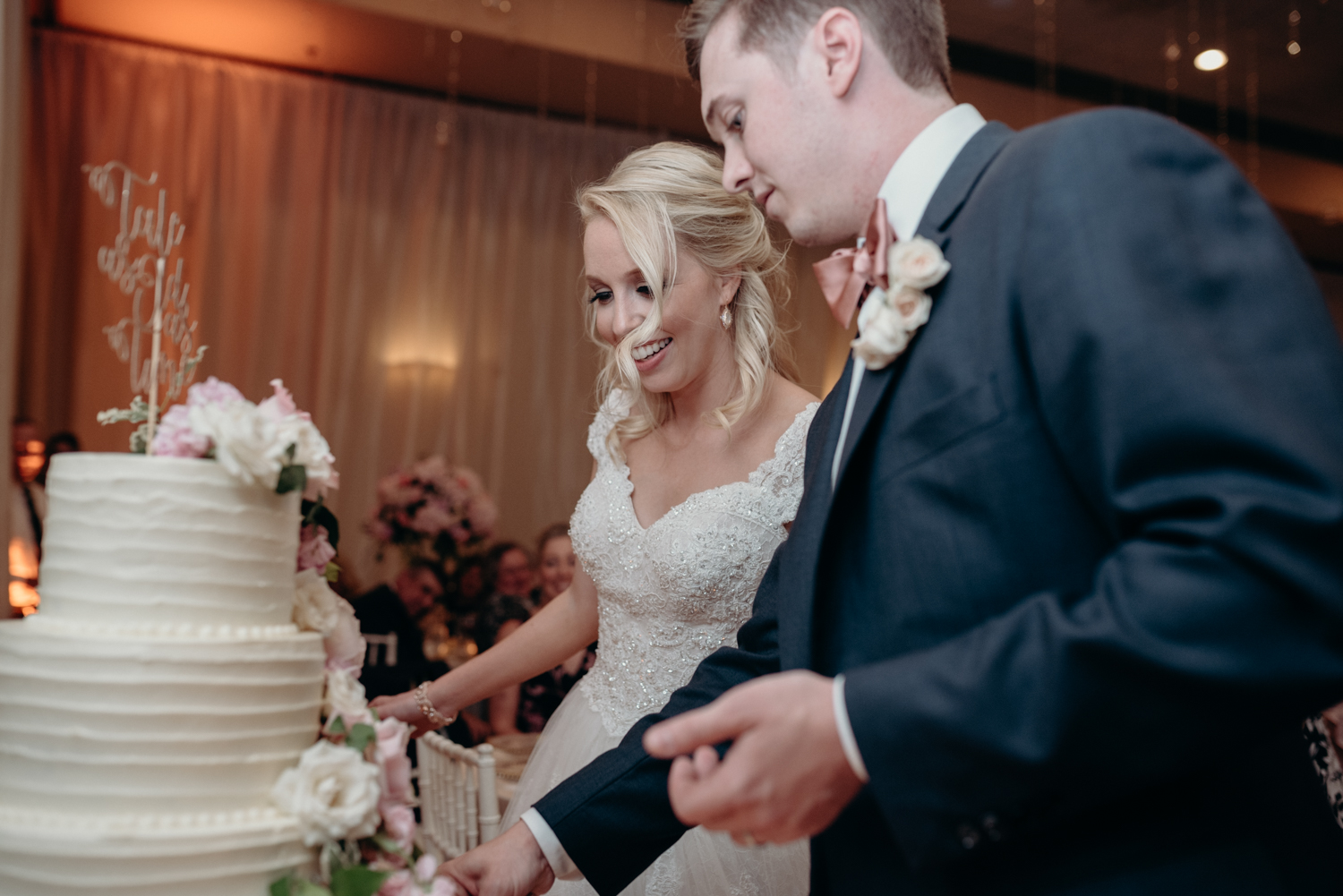 A bride and groom cut the cake at their wedding reception at Lansdowne Resort.