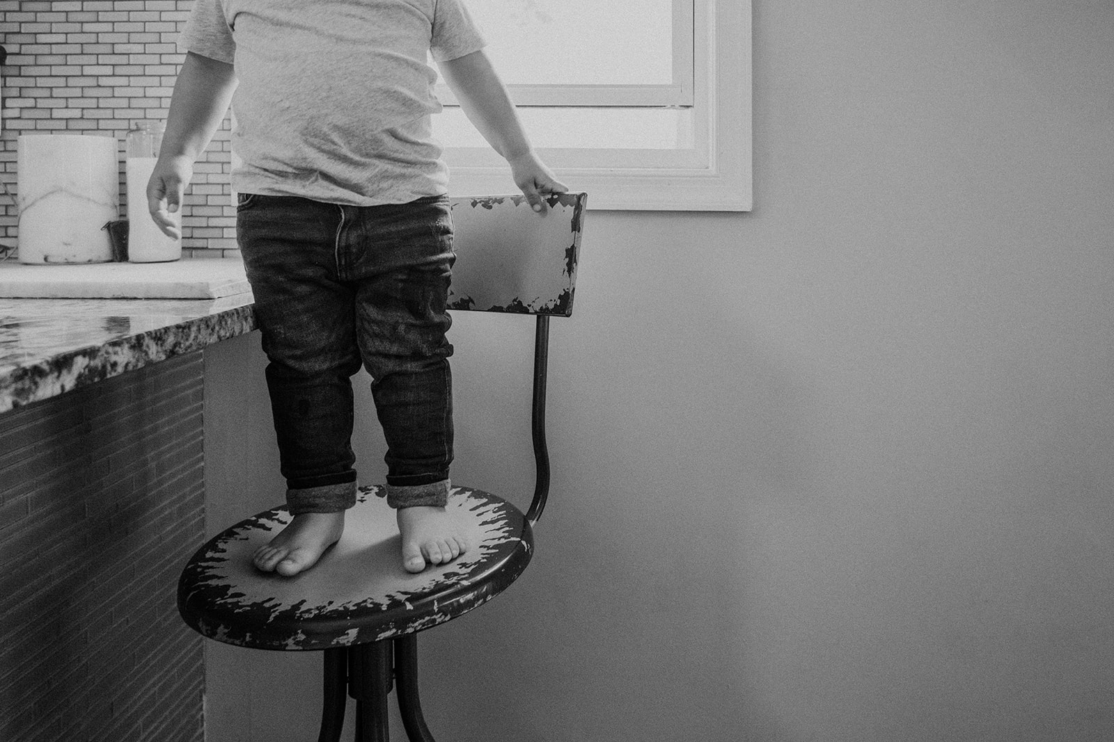 A little boy stands on a chair by the kitchen island in his home during an in-home family photography session.
