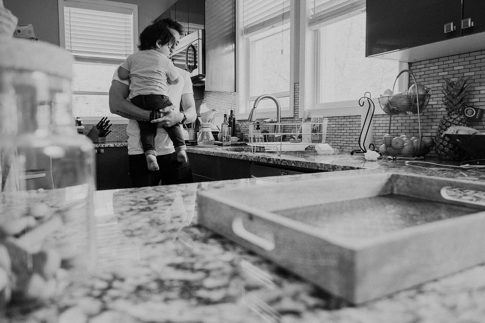 A father holds his son in the kitchen of their DC home during an in-home family photography session.