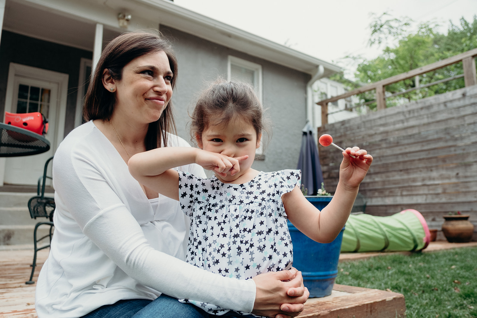 A little girl holds up her lollipop while sitting with her mother on the back deck of their DC home during an in-home family photography session.