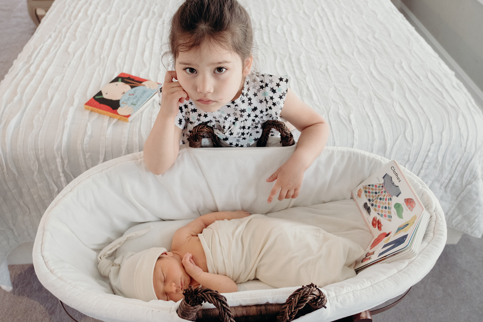 A little girl sits next to her baby brother in his bassinet during an in-home family photography session.