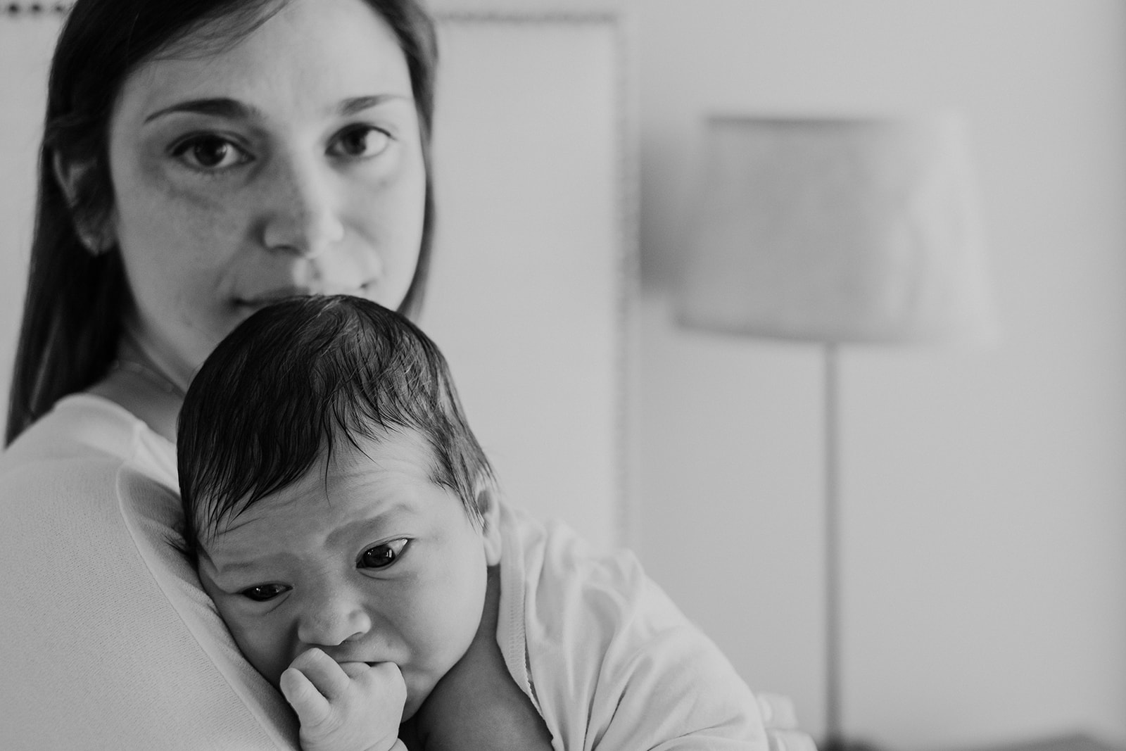 A mother holds her son after nursing him during and in home family photography session.