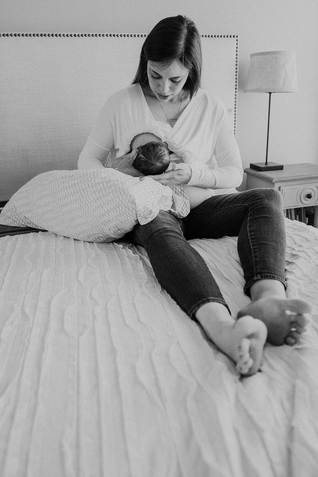 A mother nurses her newborn son on her bed during an in-home family photography session.