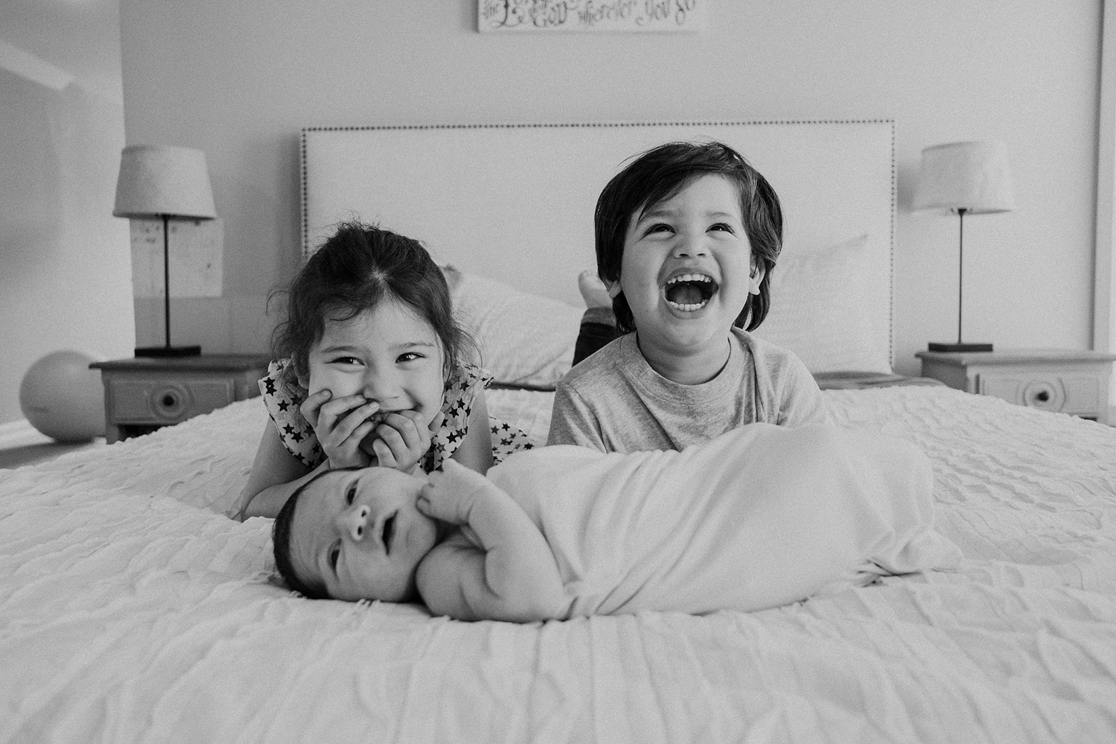 A brother and sister giggle while their baby brother lies in front of them during an in home family photography session.