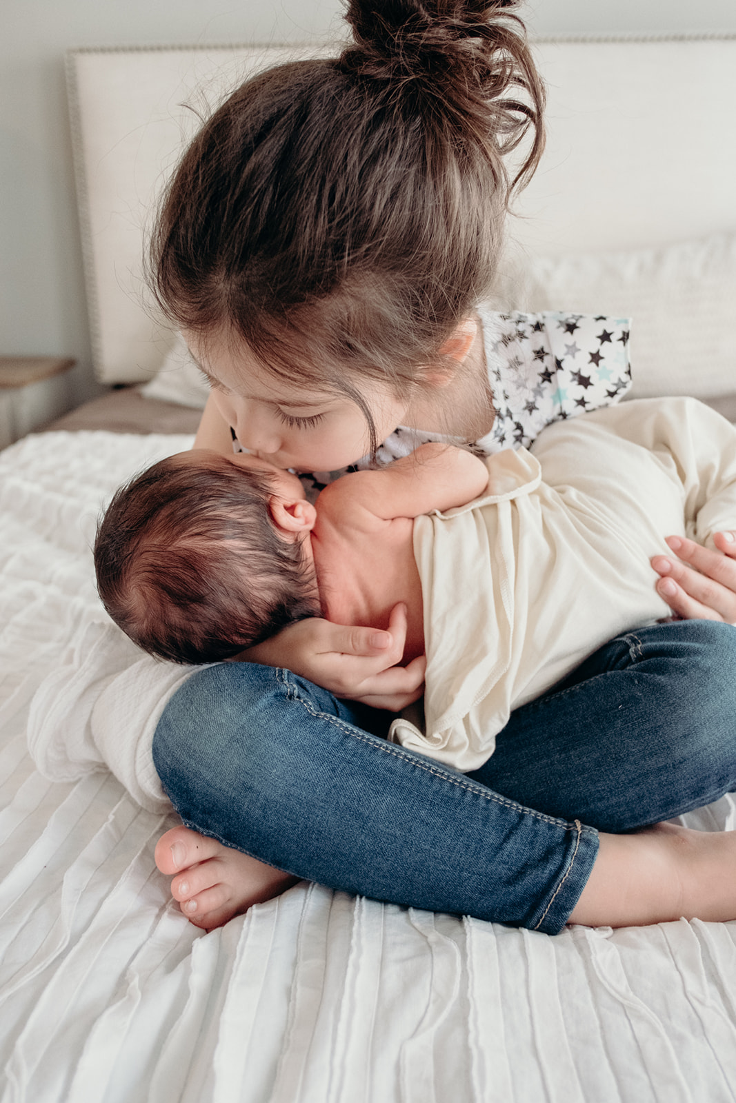 A little girl kisses her baby brother while she holds him on her lap during an in-home family photography session.