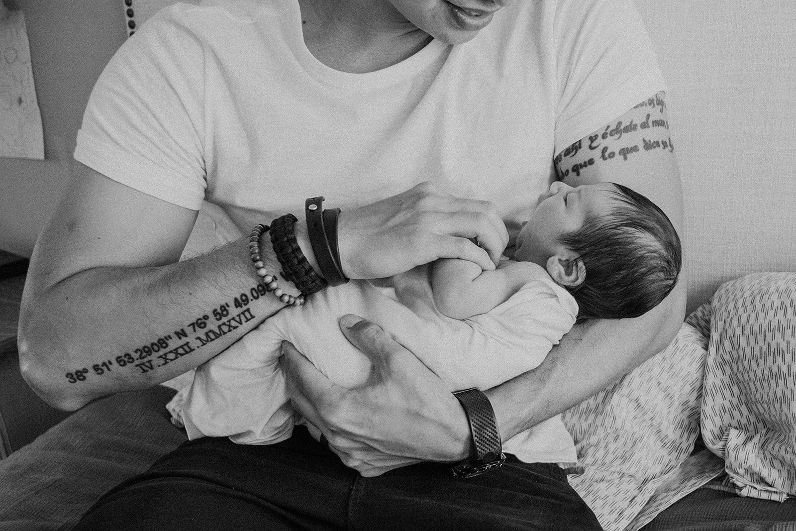 A tattooed father holds his newborn son during an in home family photography session.