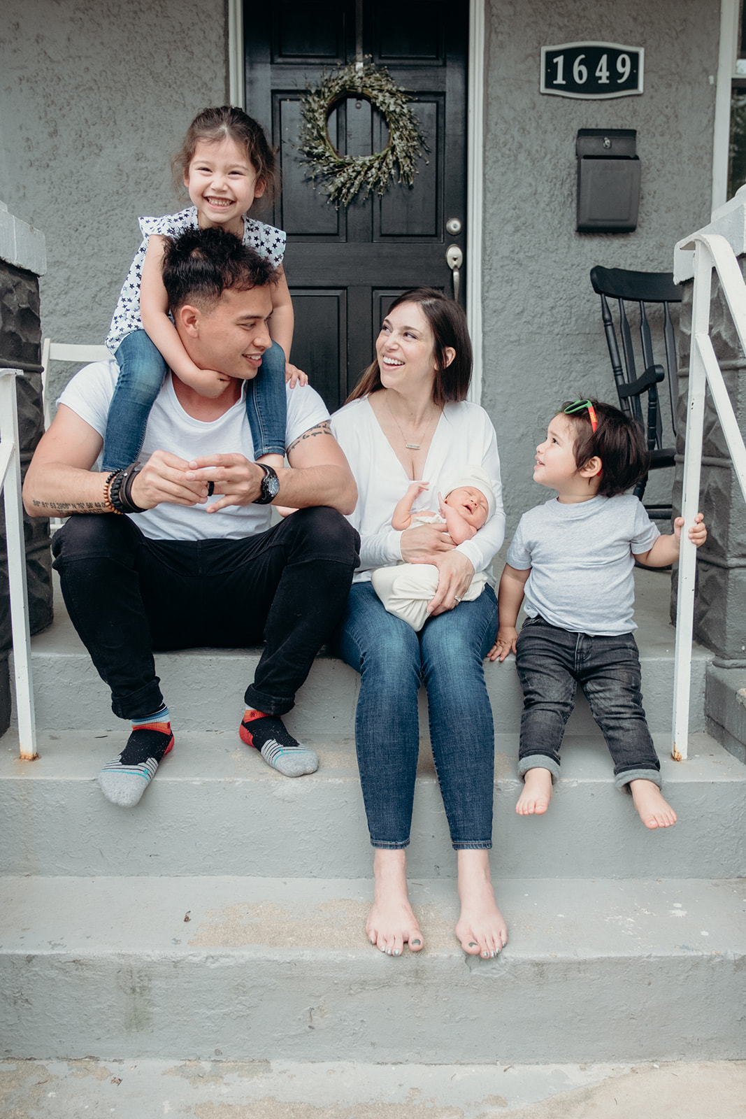 A family enjoys their front porch while snuggling their newborn in DC during an in home family photography session.