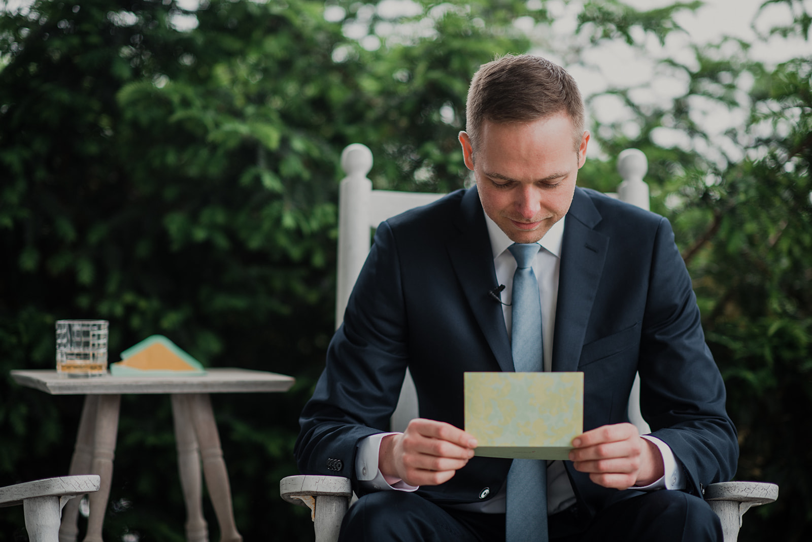 A groom reads a letter from his bride on the front porch of the house at Blue Hill Farm in Waterford, VA.