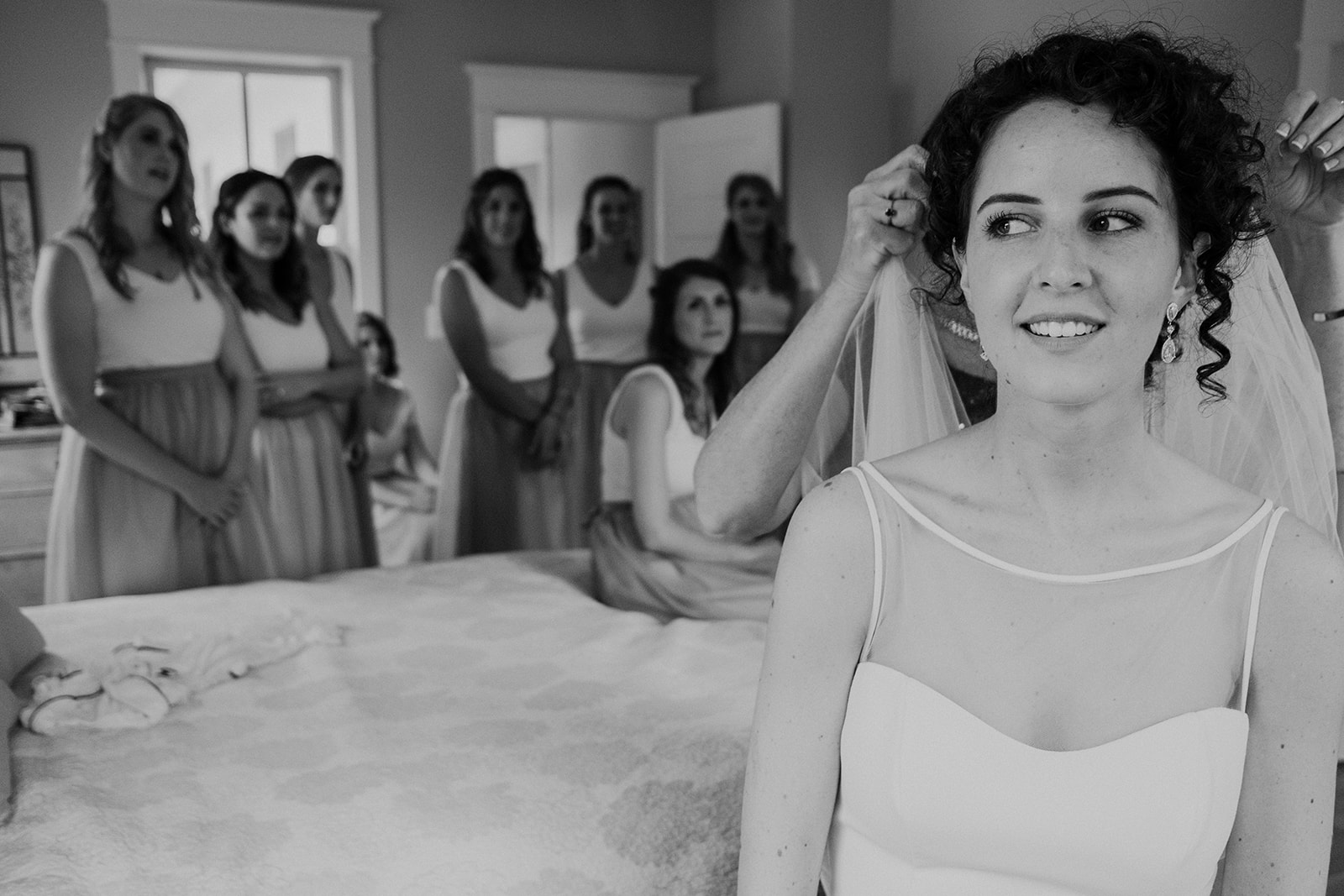 Bridesmaids look on while a bride gets her veil put in place before her outdoor wedding ceremony at Blue Hill Farm in Waterford, VA.