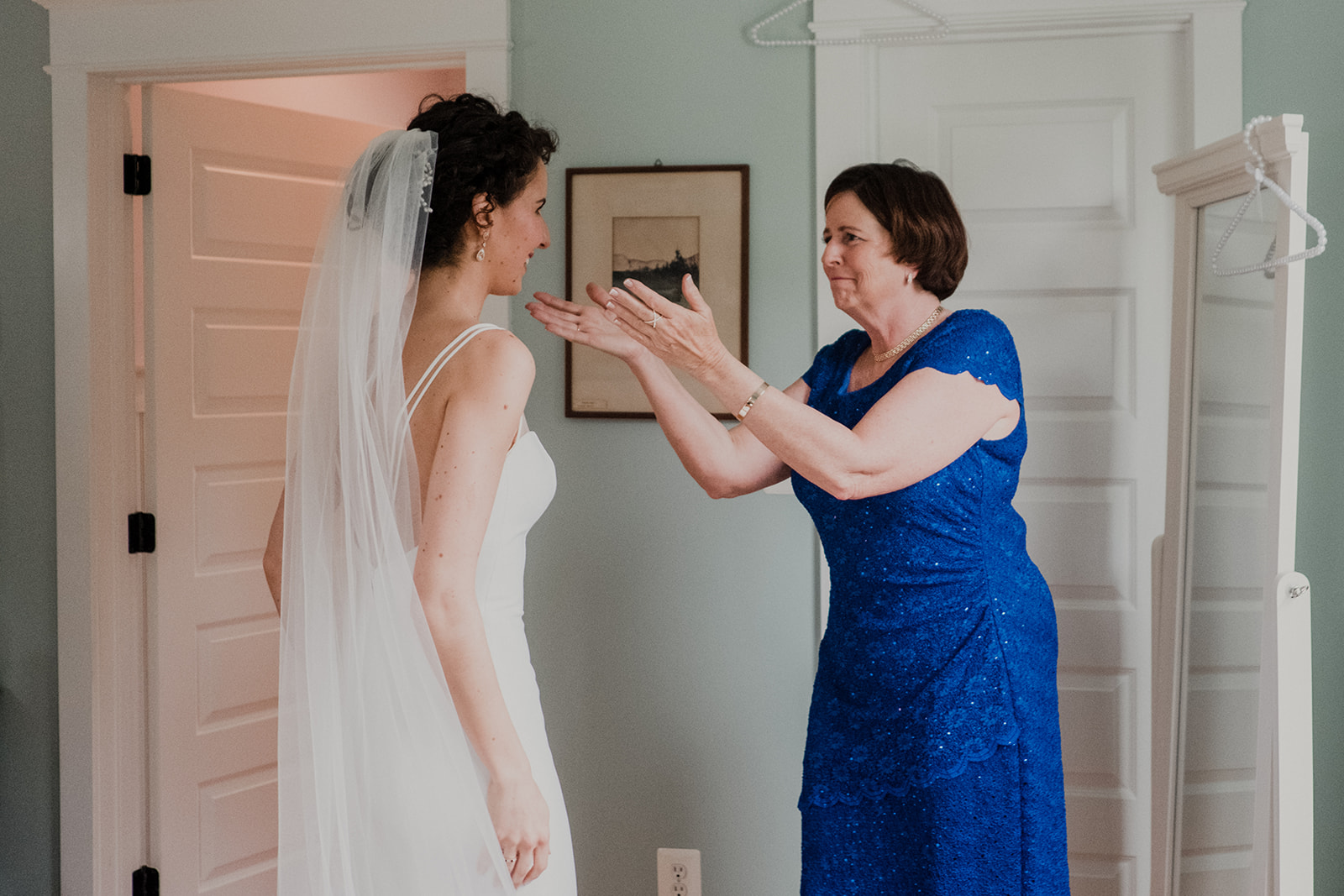 The mother of the bride reaches out to her daughter on her wedding day at Blue Hill Farm in Waterford, VA.