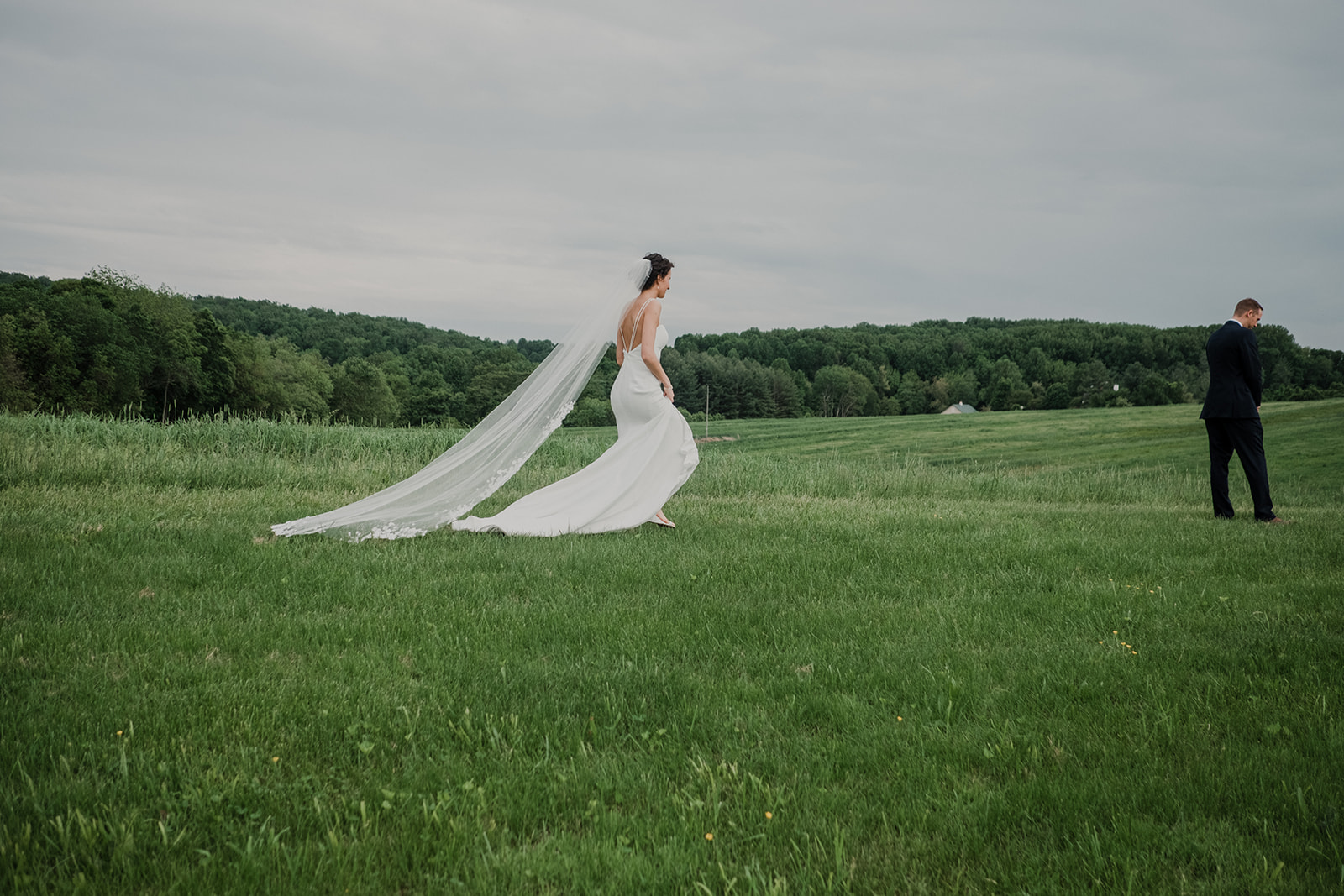 A bride with a long veil walks through a field towards her groom for a first look before their outdoor wedding ceremony at Blue Hill Farm in Waterford, VA.