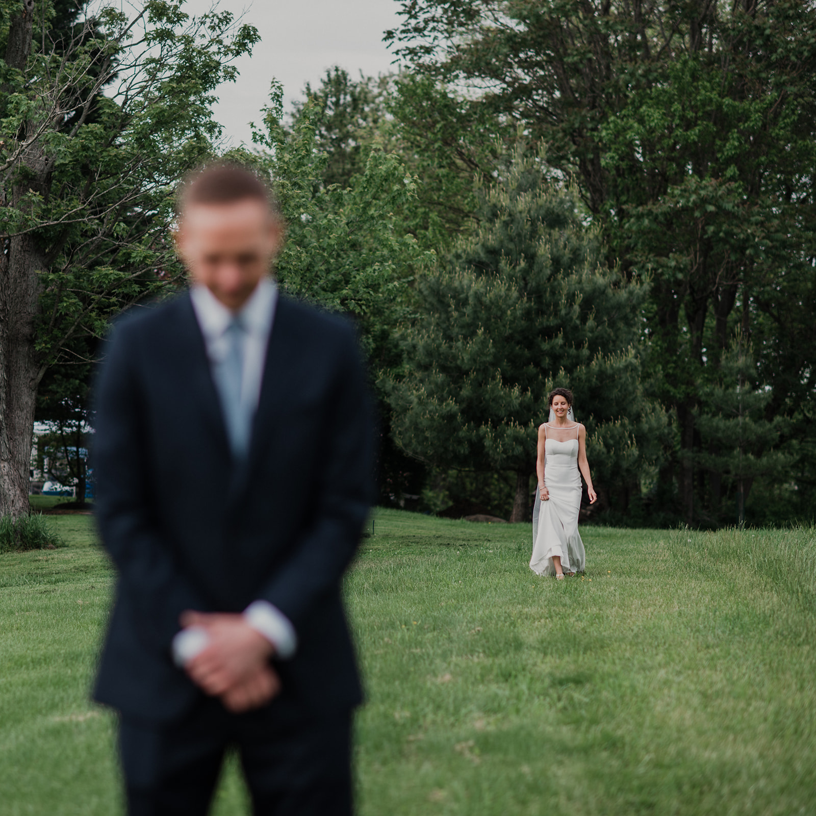 A groom waits while his bride walks up behind him for a first look before their outdoor wedding ceremony at Blue Hill Farm in Waterford, VA.