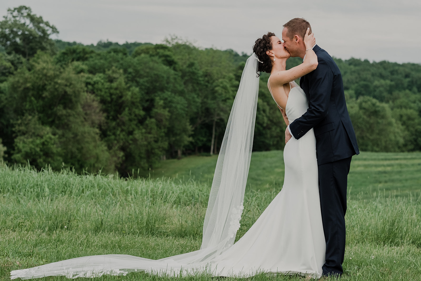 A bride and groom kiss during their first look before their outdoor wedding ceremony at Blue Hill Farm in Waterford, VA.