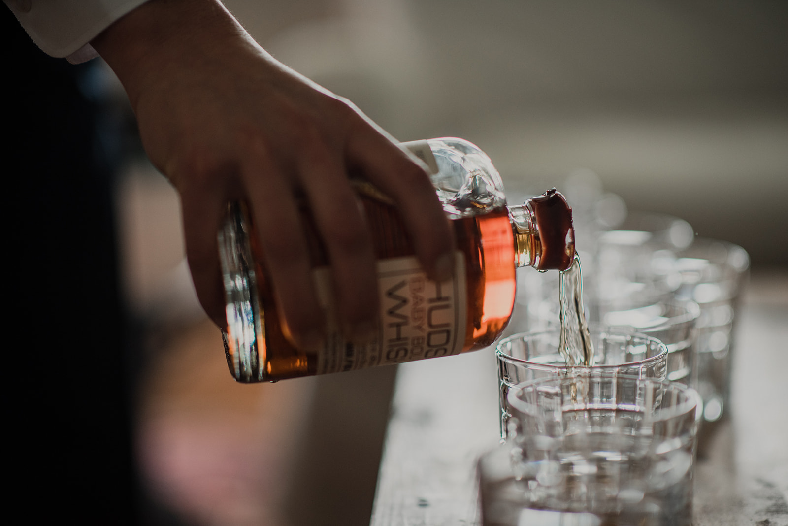 A groomsman pours bourbon into glasses for a toast before an outdoor wedding ceremony at Blue Hill Farm in Waterford, VA.