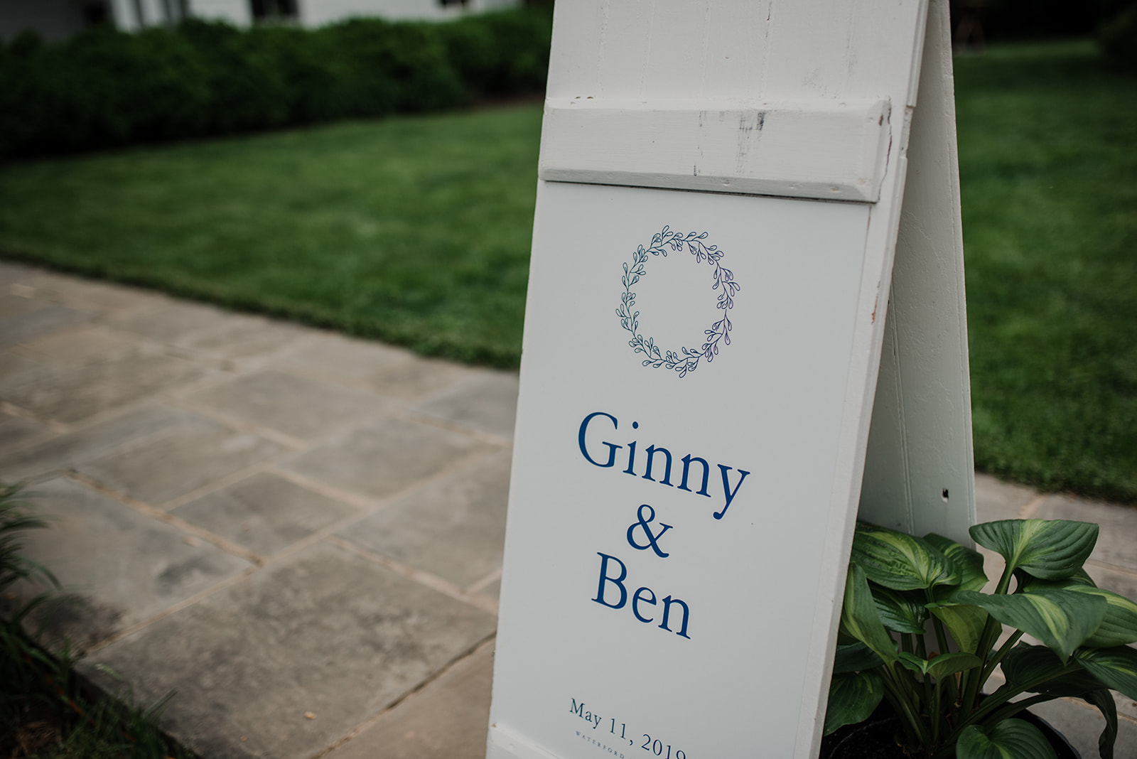 The bride and groom's names appear on a sign outside of their outdoor wedding ceremony at Blue Hill Farm in Waterford, VA.