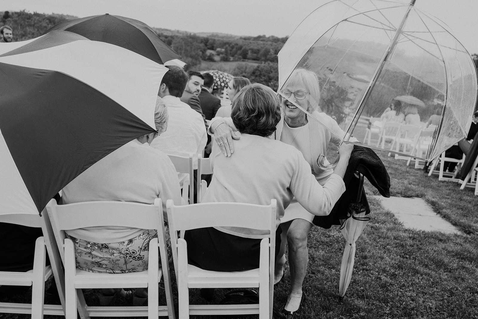 Guests hug under an umbrella at a spring outdoor wedding ceremony at Blue Hill Farm in Waterford, VA.