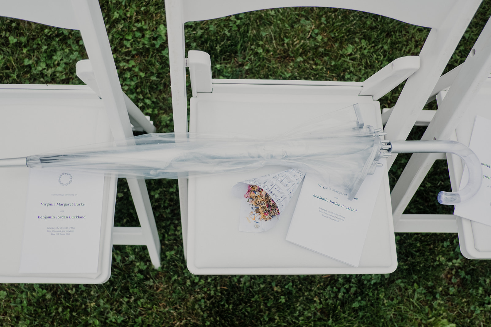 An umbrella sits next to the programs at an outdoor wedding ceremony at Blue Hill Farm in Waterford, VA.