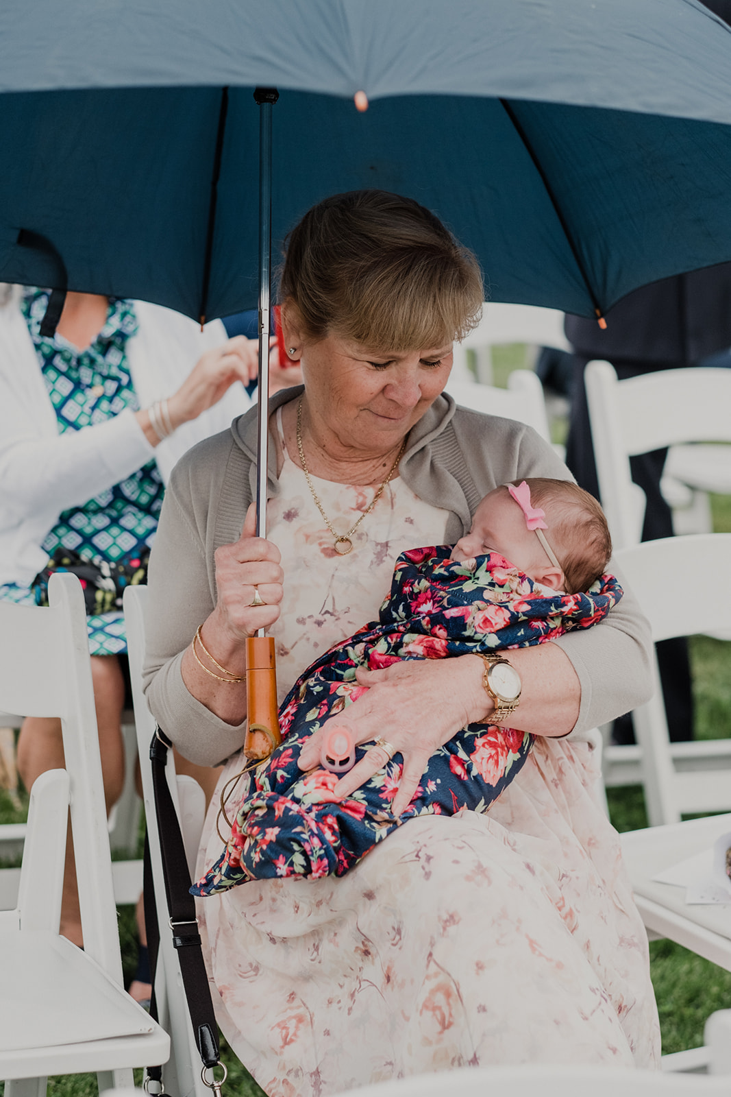 A grandmother holds her swaddled granddaughter under an umbrella at an outdoor wedding ceremony at Blue Hill Farm in Waterford, VA.
