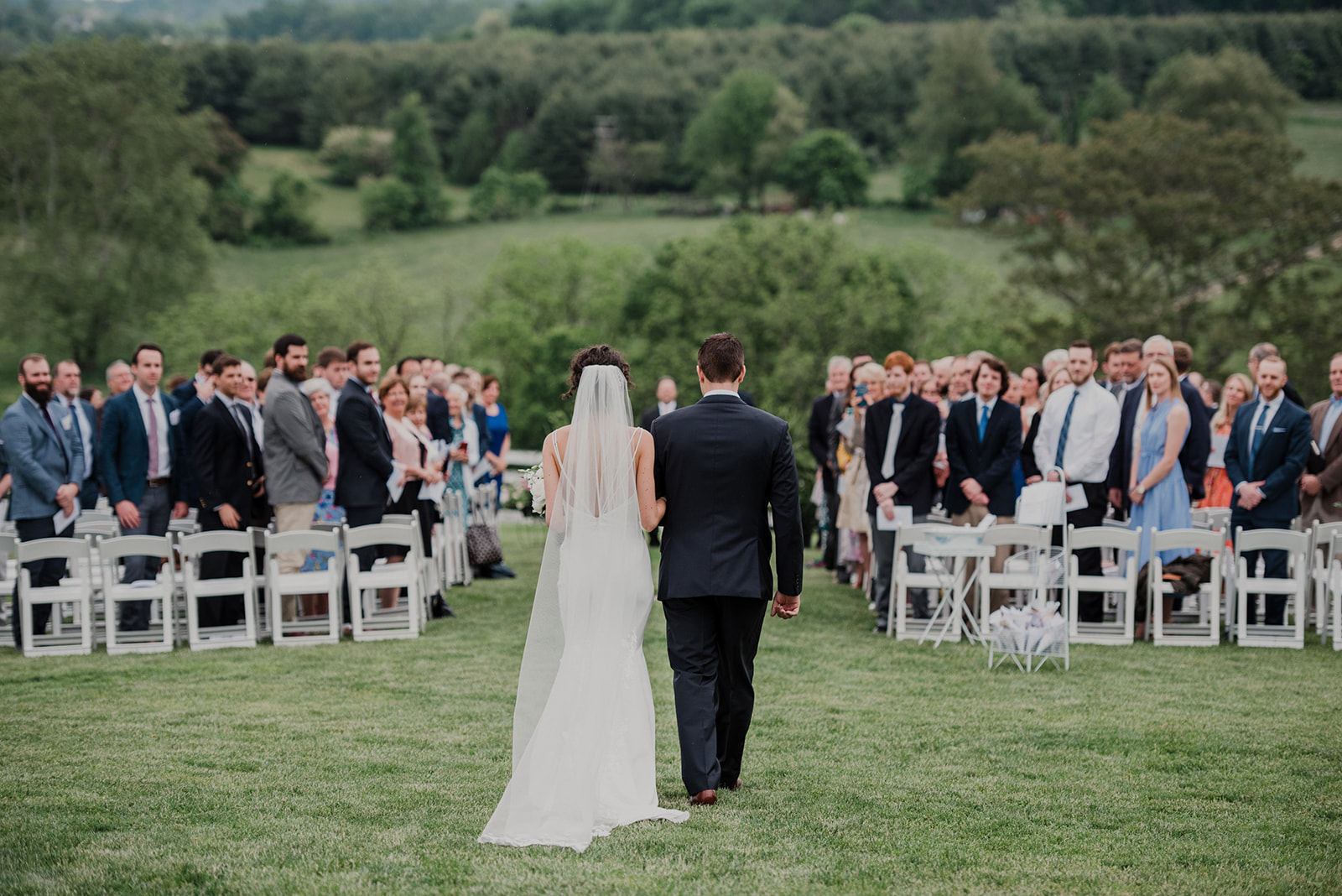 A bride is escorted by her brother to her outdoor wedding ceremony at Blue Hill Farm in Waterford, VA.