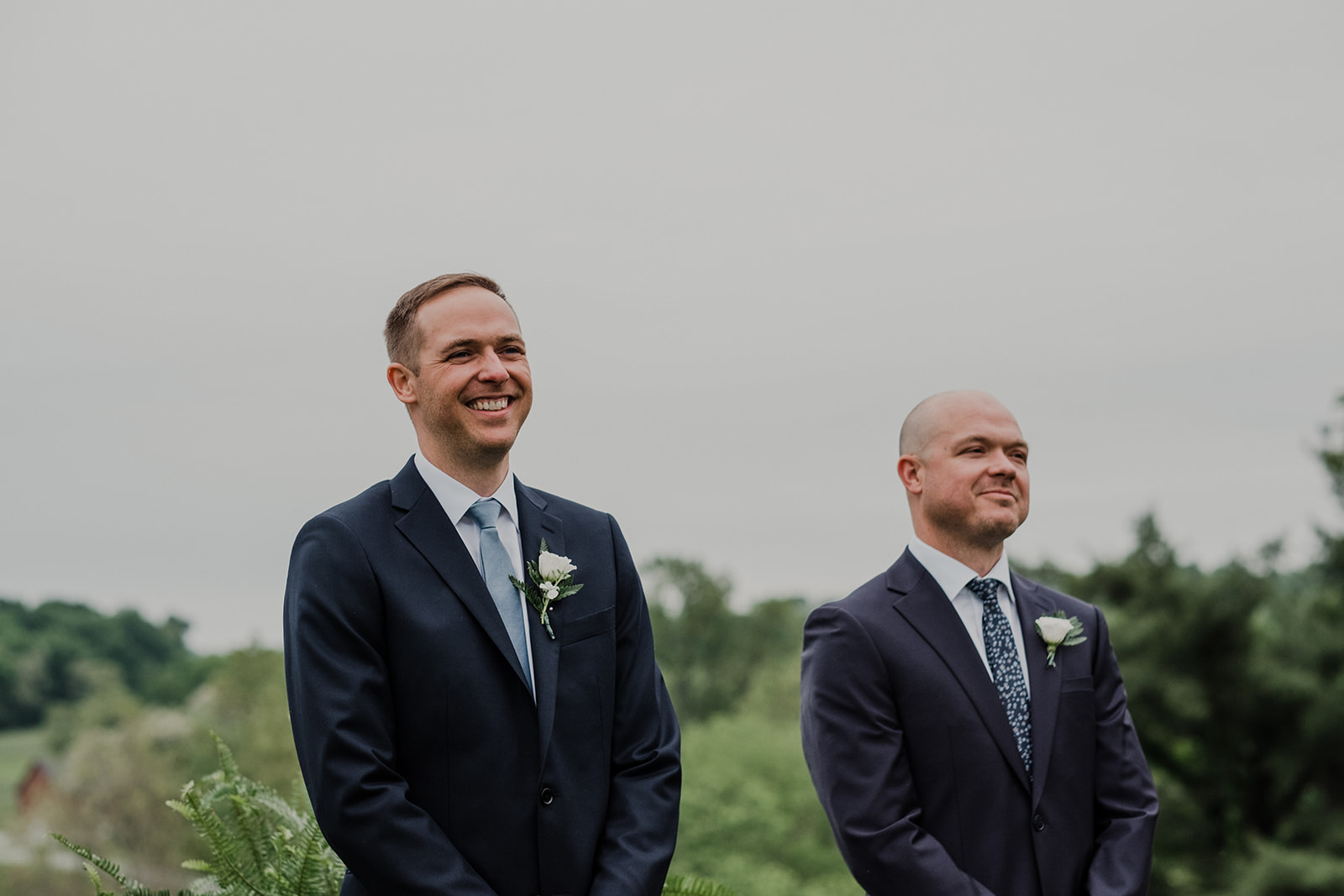 A groom smiles as he watches his bride walk down the aisle at their outdoor wedding ceremony at Blue Hill Farm in Waterford, VA.