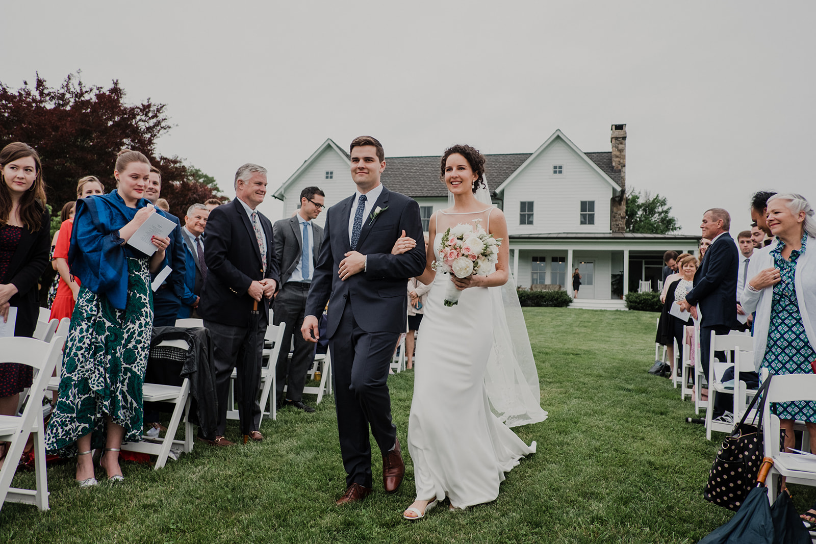 A bride is escorted by her brother down the aisle of her outdoor wedding at Blue Hill Farm in Waterford, VA.