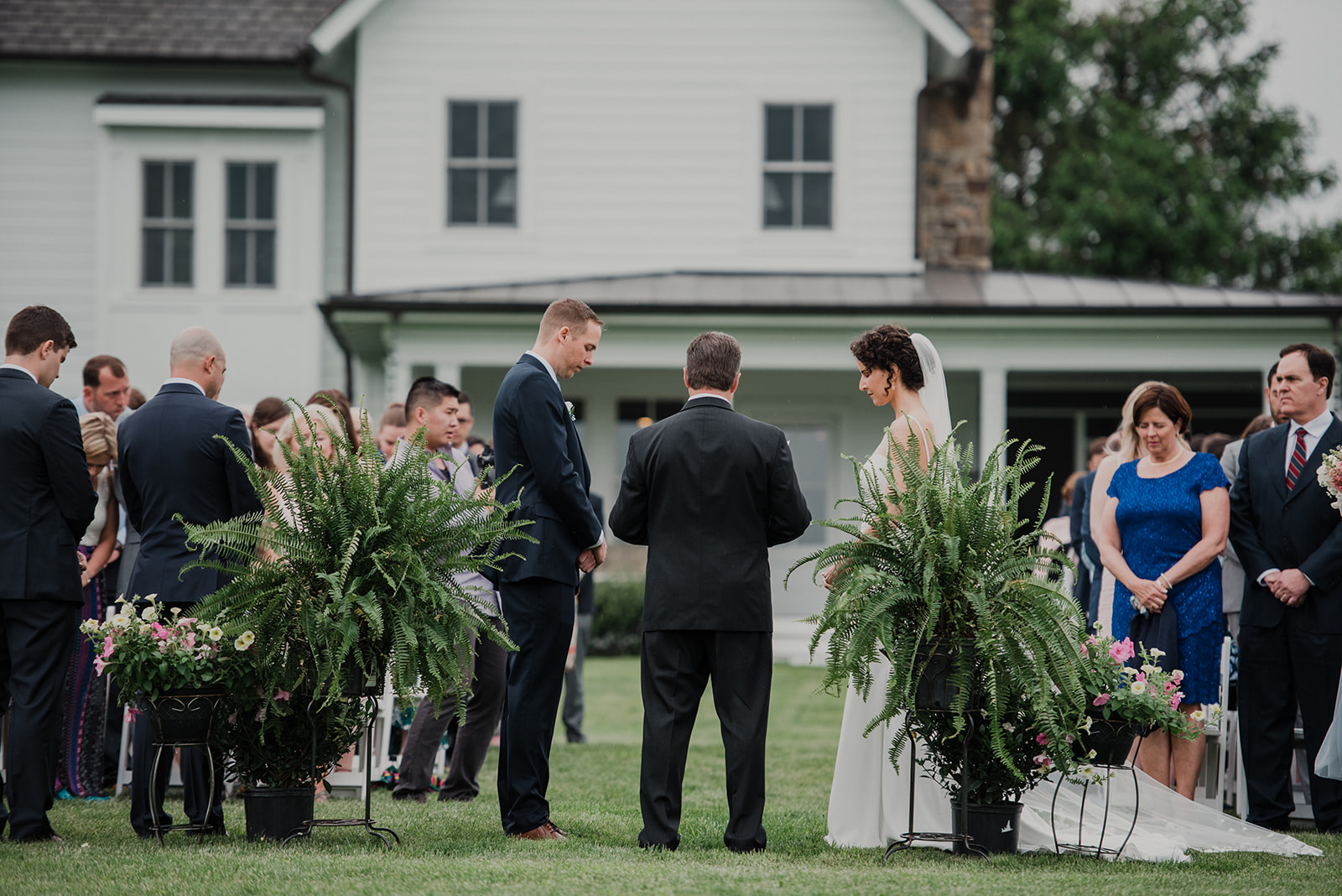 A bride and a groom get married between two ferns during their outdoor wedding ceremony at Blue Hill Farm in Waterford, VA.