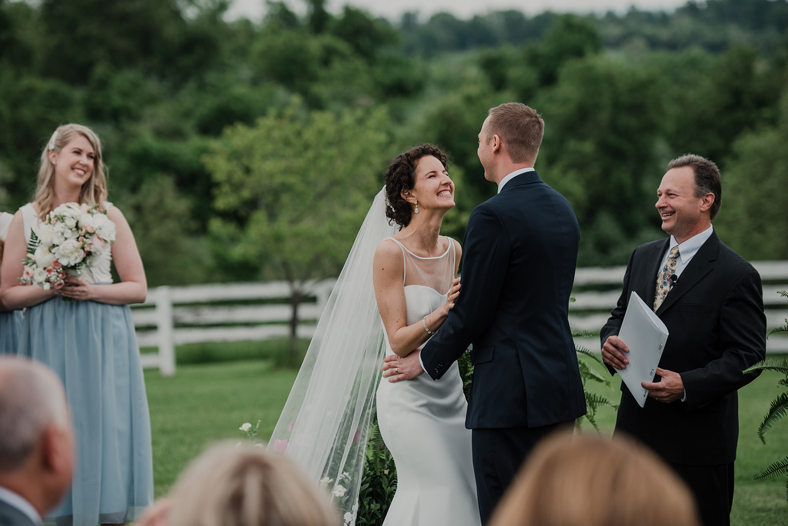 A newly pronounced husband and wife are all smiles during their outdoor wedding ceremony at Blue Hill Farm in Waterford, VA.
