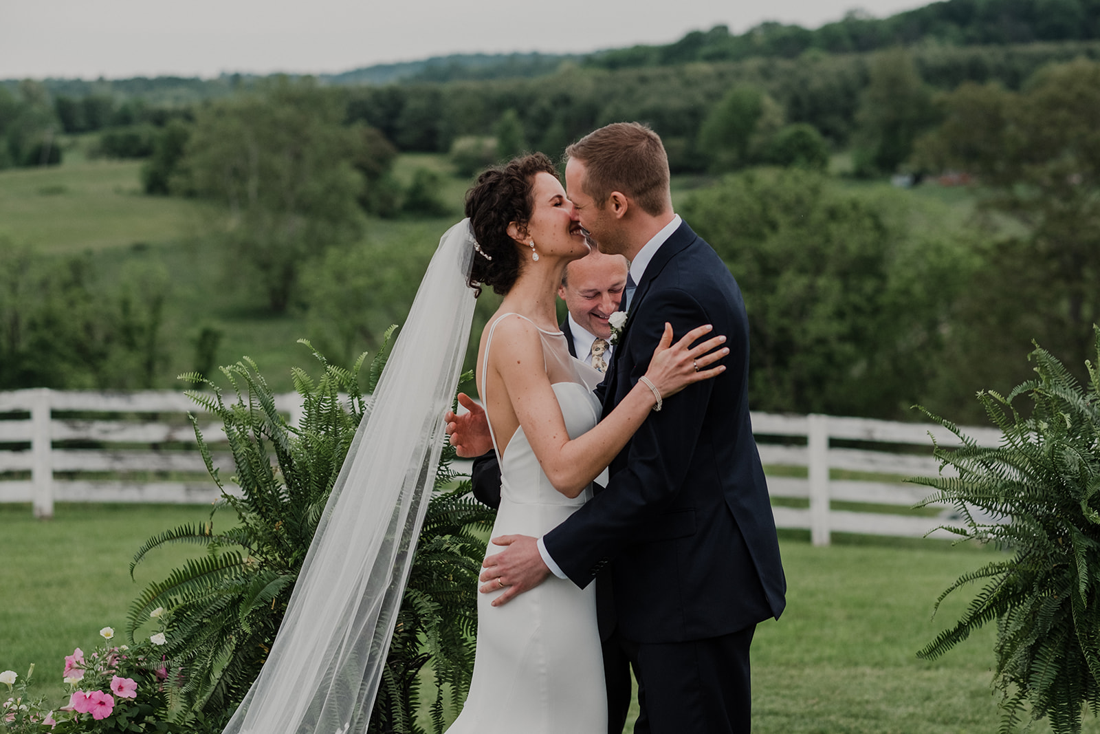 A bride and groom kiss after they are pronounced husband and wife during their outdoor wedding ceremony at Blue Hill Farm in Waterford, VA.