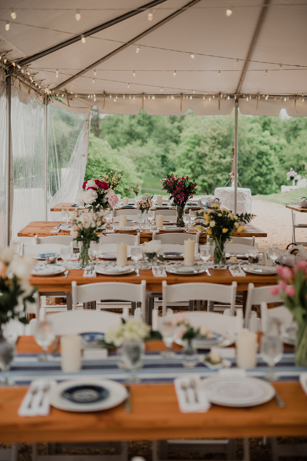 Farm tables are adorned with wildflower bouquets and blue ceramic plates at a wedding reception at Blue Hill Farm in Waterford, VA.