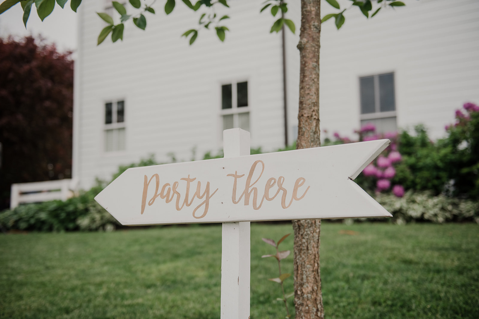 A sign denotes where the party is for a wedding reception at Blue Hill Farm in Waterford, VA.