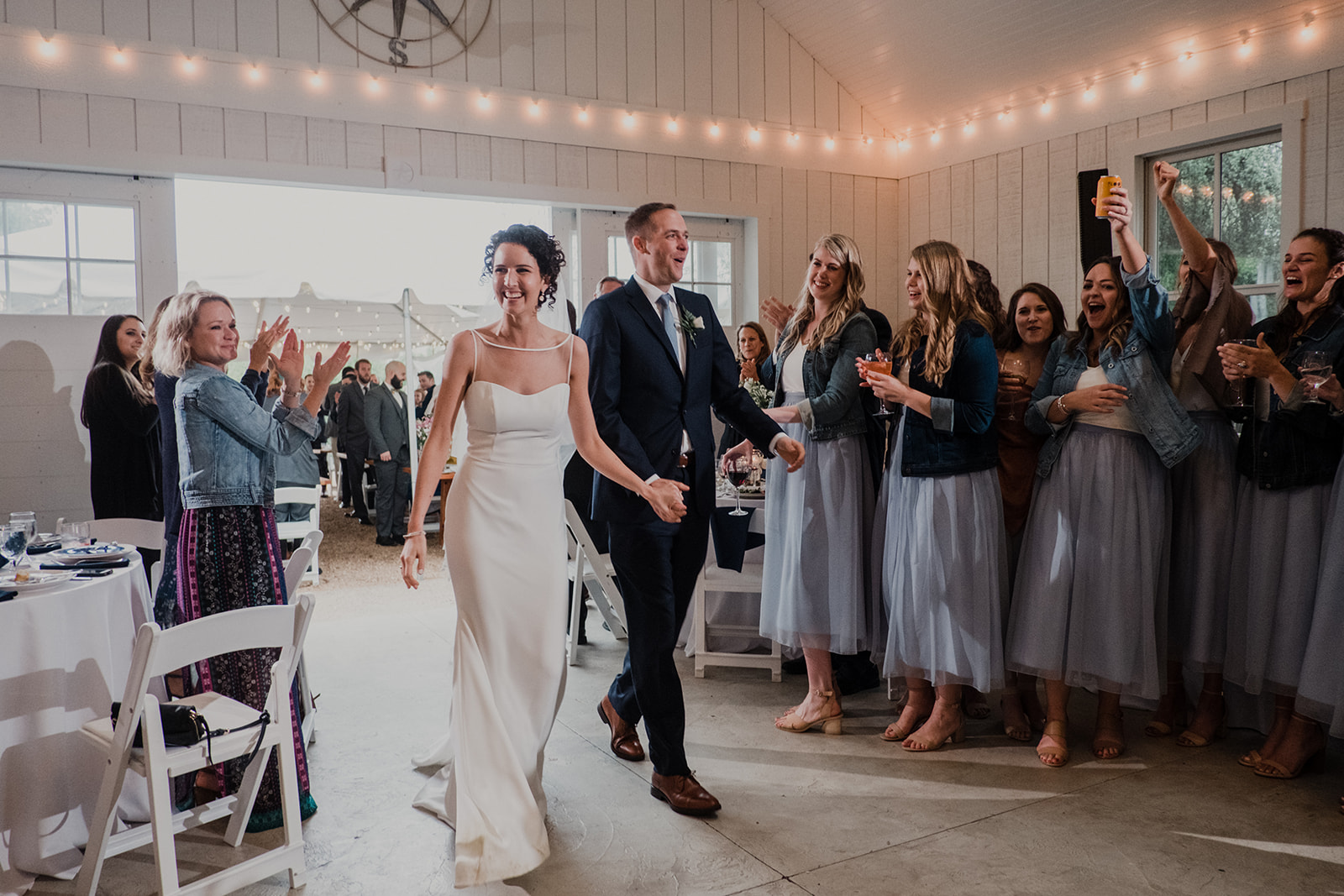 A bride and groom are applauded by guests as they walk into their wedding reception at Blue Hill Farm in Waterford, VA