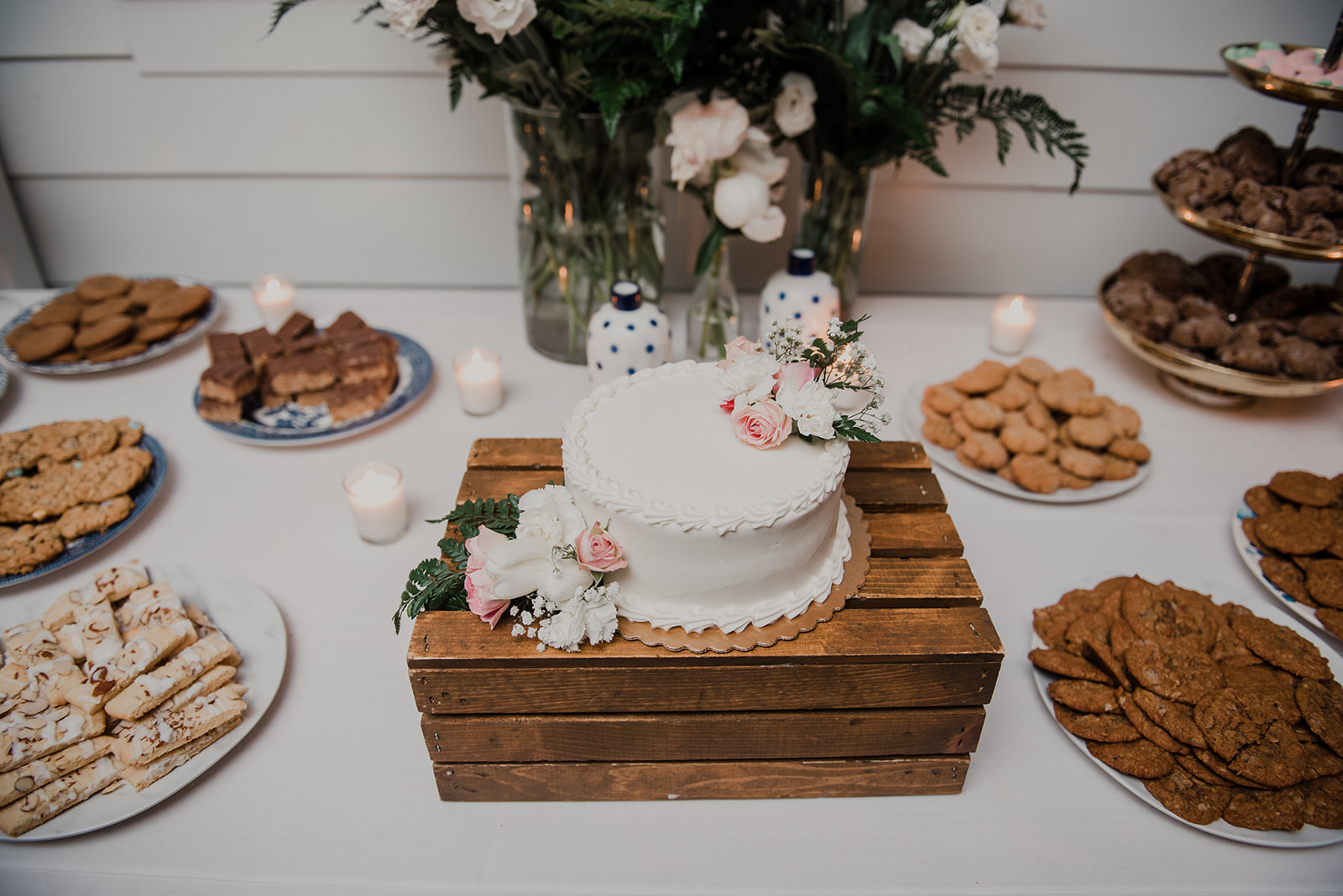A white buttercream cake sits on a rustic wooden crate surrounded by other desserts at a wedding reception at Blue Hill Farm in Waterford, VA.