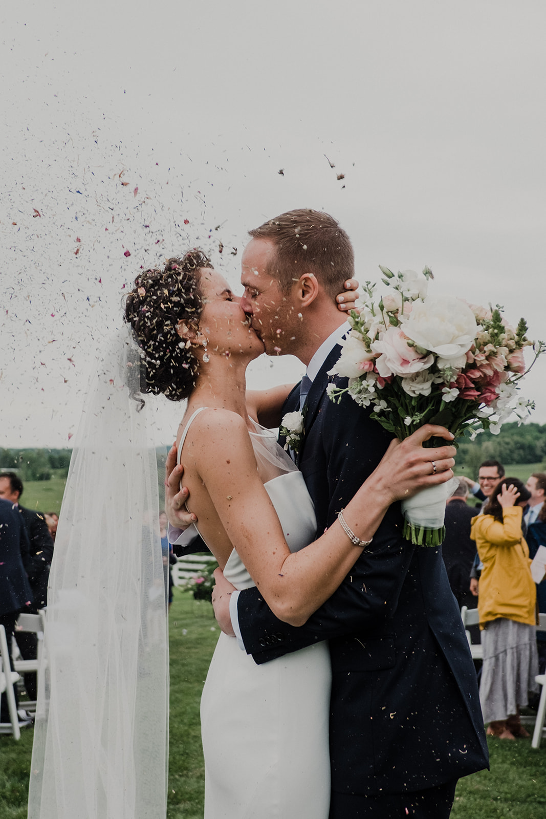 A bride and groom kiss in the aisle after their outdoor wedding ceremony at Blue Hill Farm in Waterford, VA as guests toss flower petal confetti.
