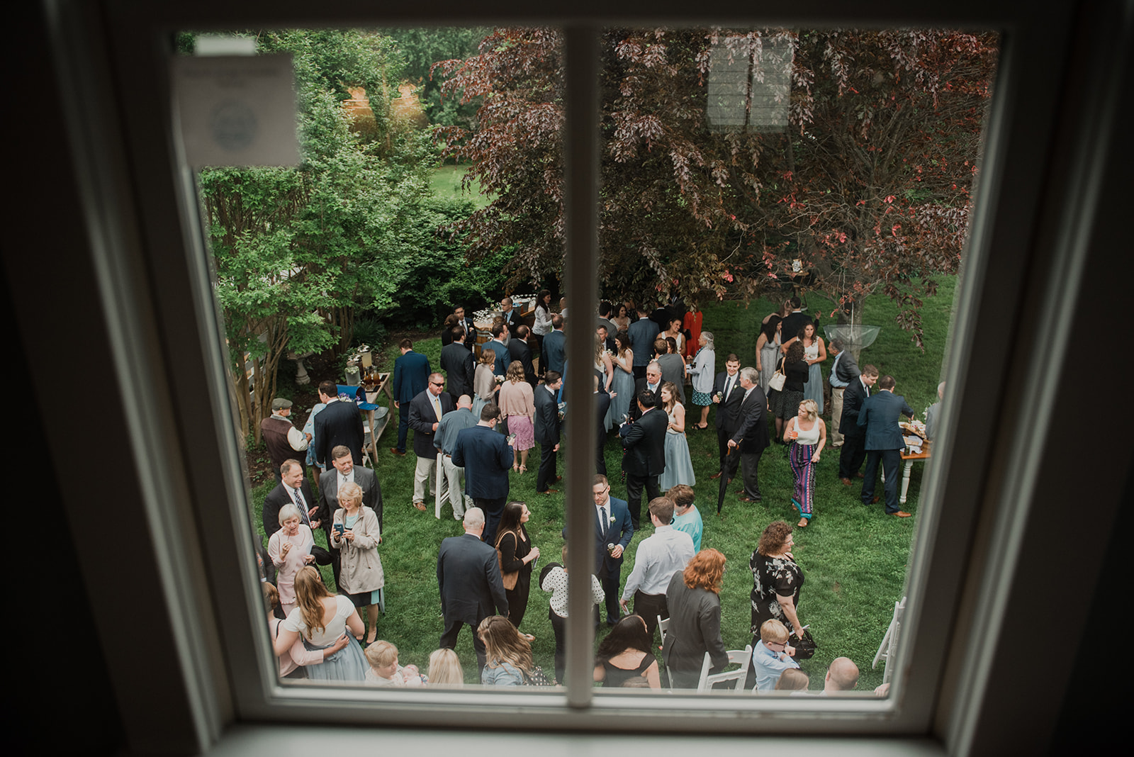 Guests are seen from above through a window enjoying cocktail hour at an outdoor wedding at Blue Hill Farm in Waterford, VA.