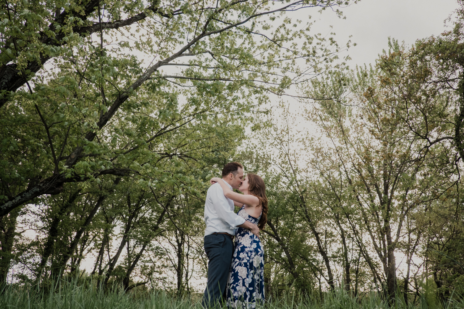 Vanish brewery engagement session virginia couple kissing in the middle of a field