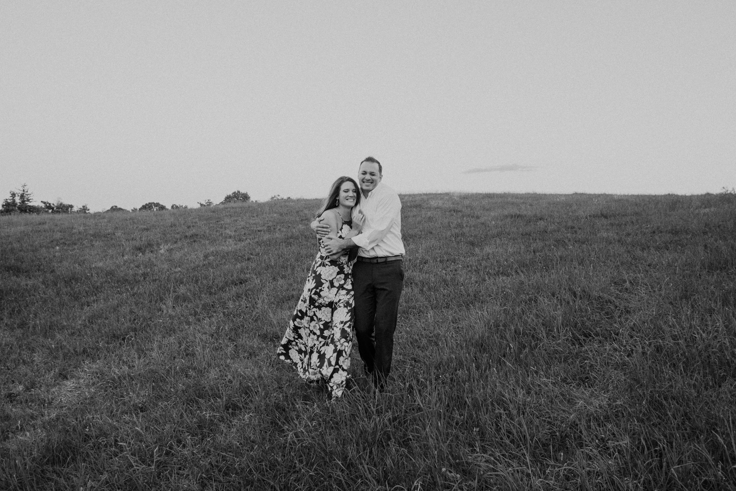 Couple walks down a hill holding each other at Morven Park during their engagement session