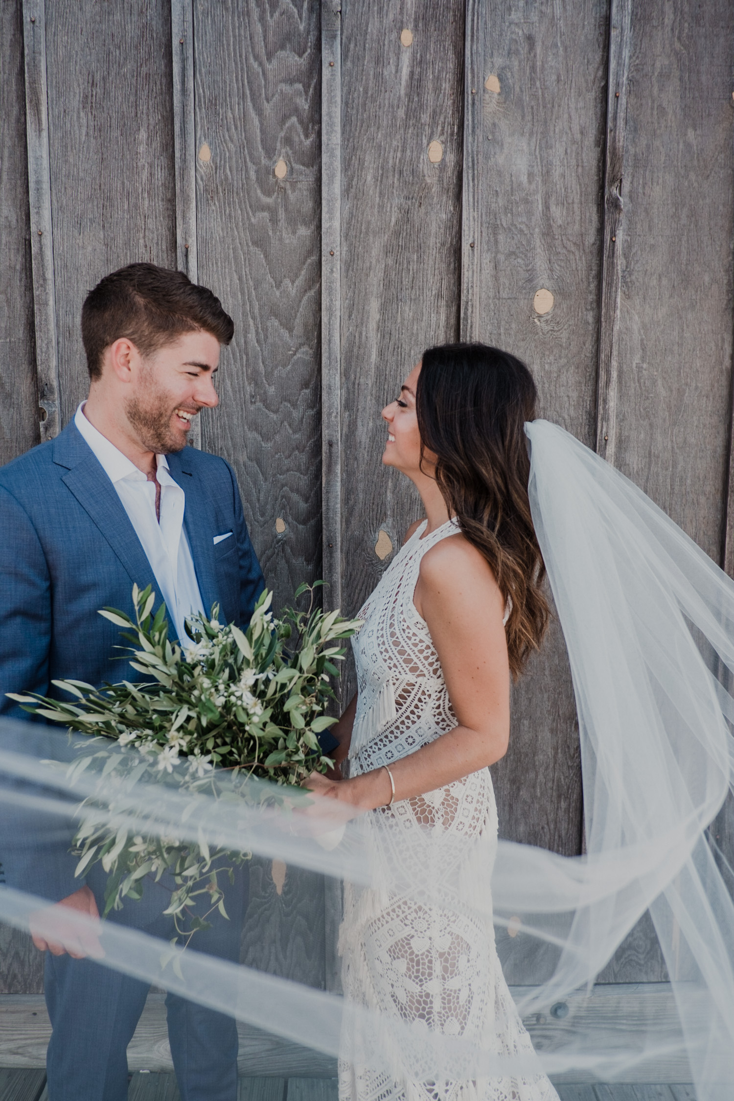 bride and groom check each other out during first look with bride's veil blowing in the wind