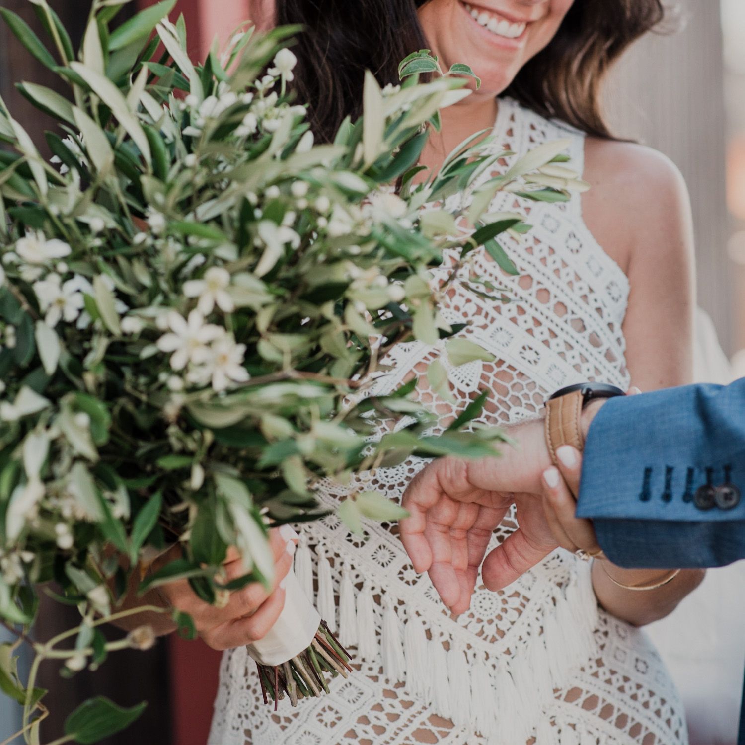 close up of bridal bouquet as bride examines her gift of a watch for the groom